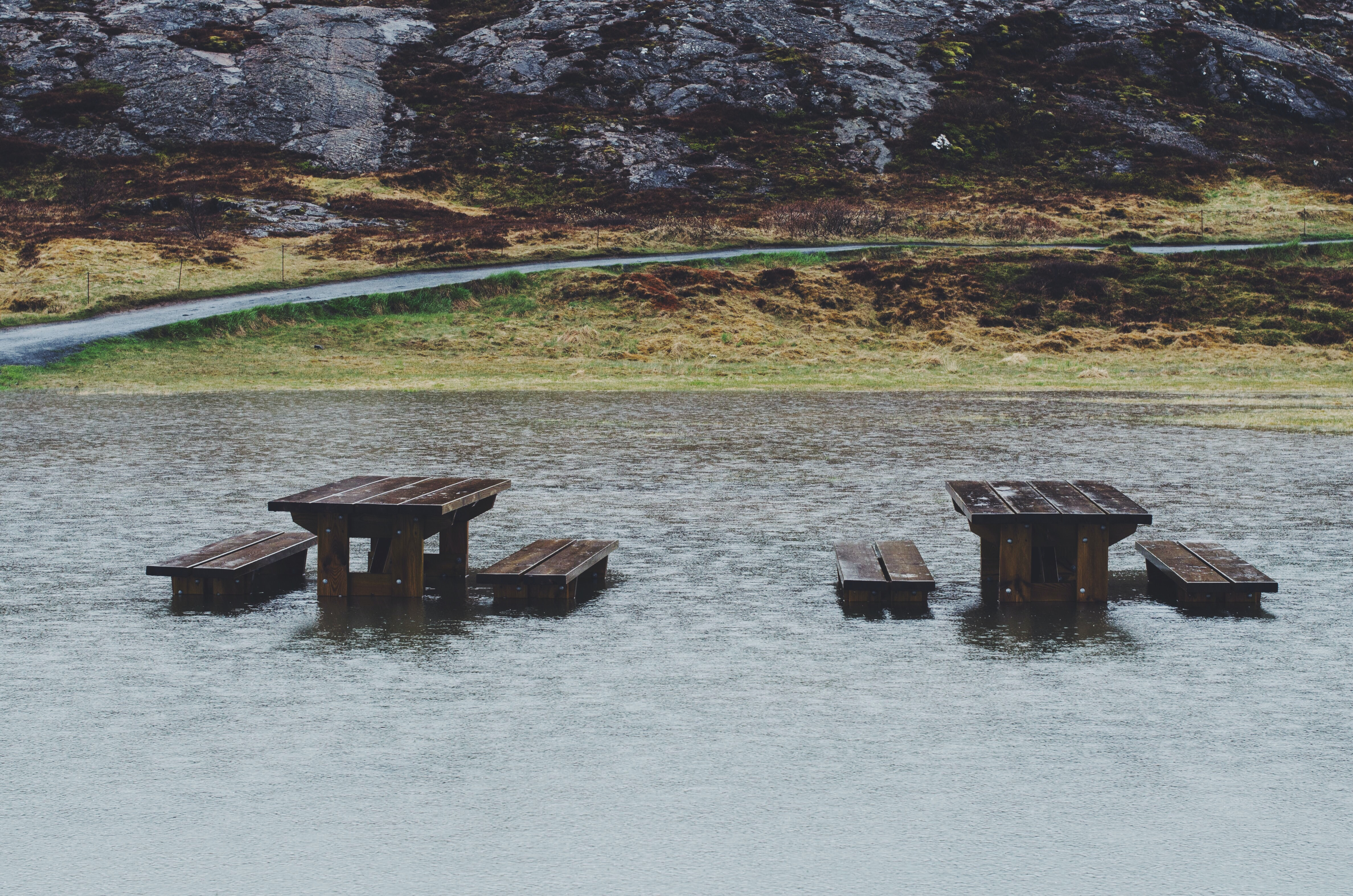 brown wooden table covered on body of water