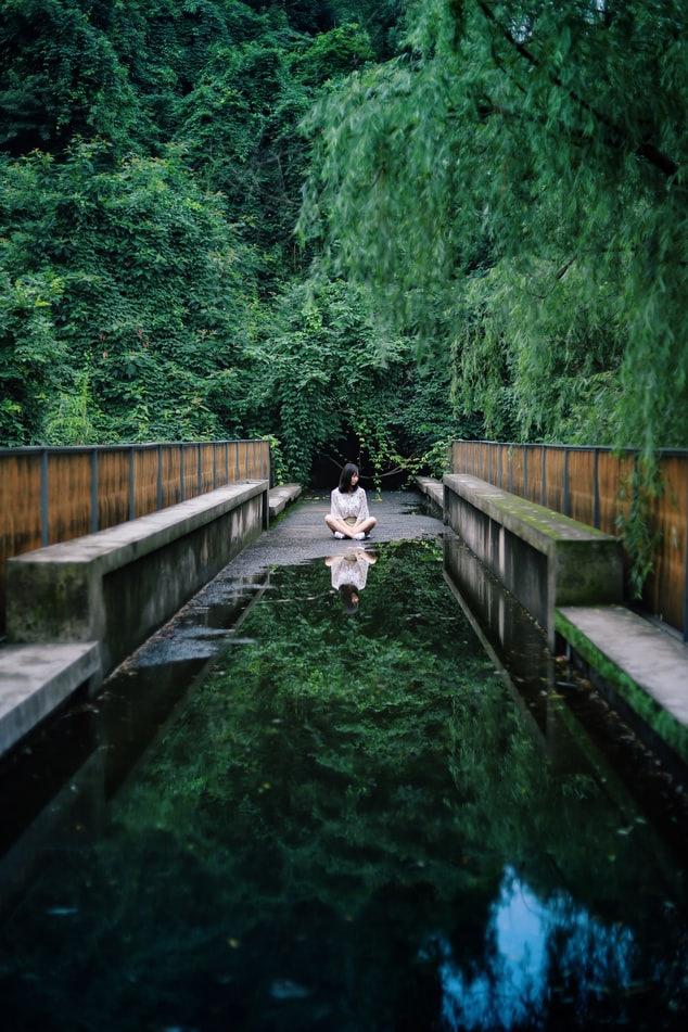 A photo of a footbridge surrounded by lush, green trees. We are looking down the bridge, it has a large puddle of water on it that reflects the trees and sky and a woman is sitting behind the puddle, cross-legged.