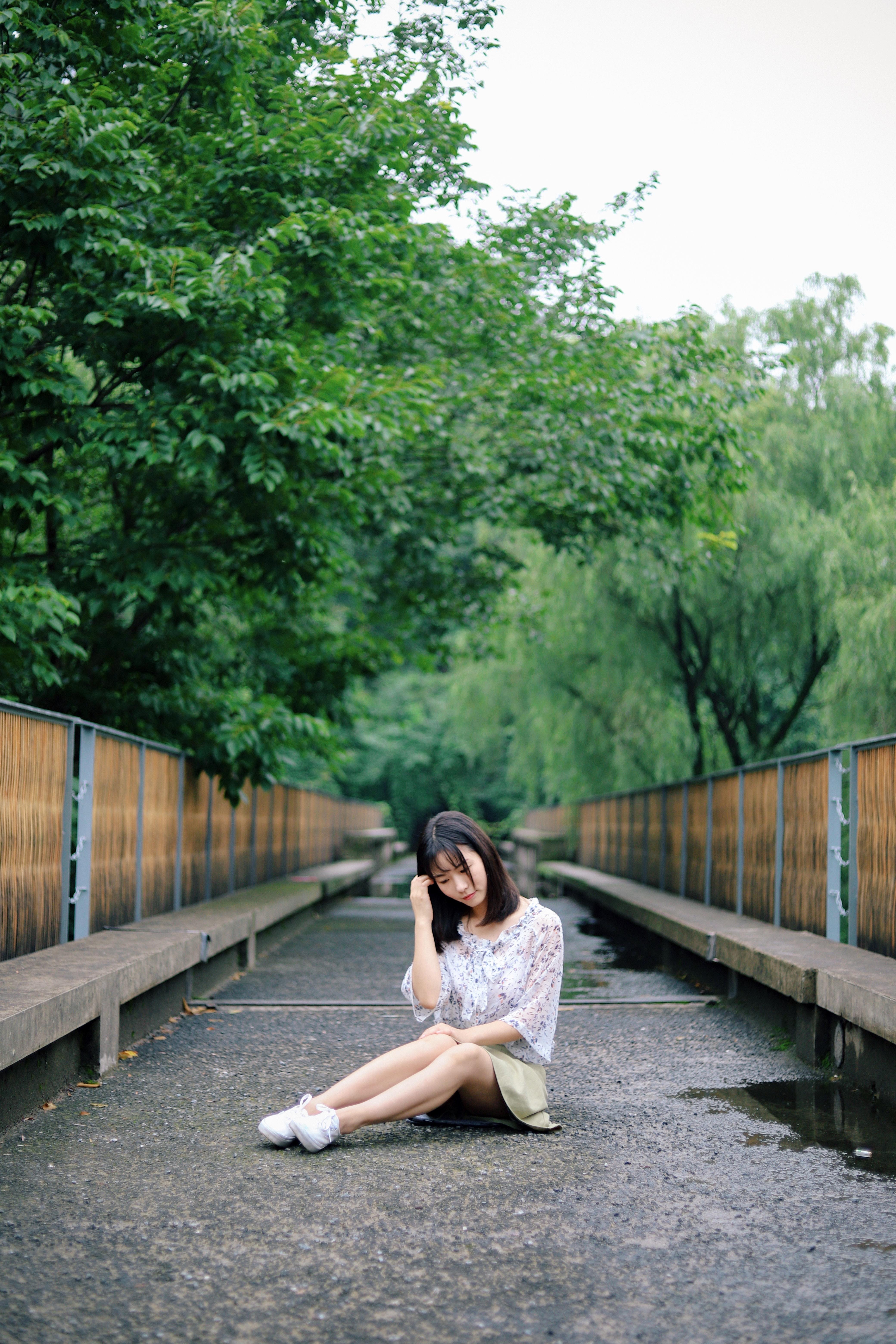 shallow focus photography of woman sitting on bridge