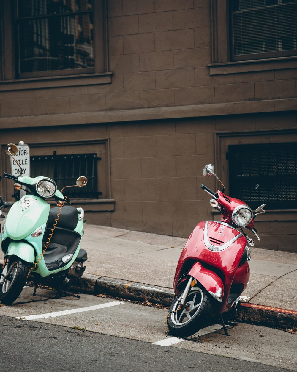 two green and red motor scooters parked on road beside building