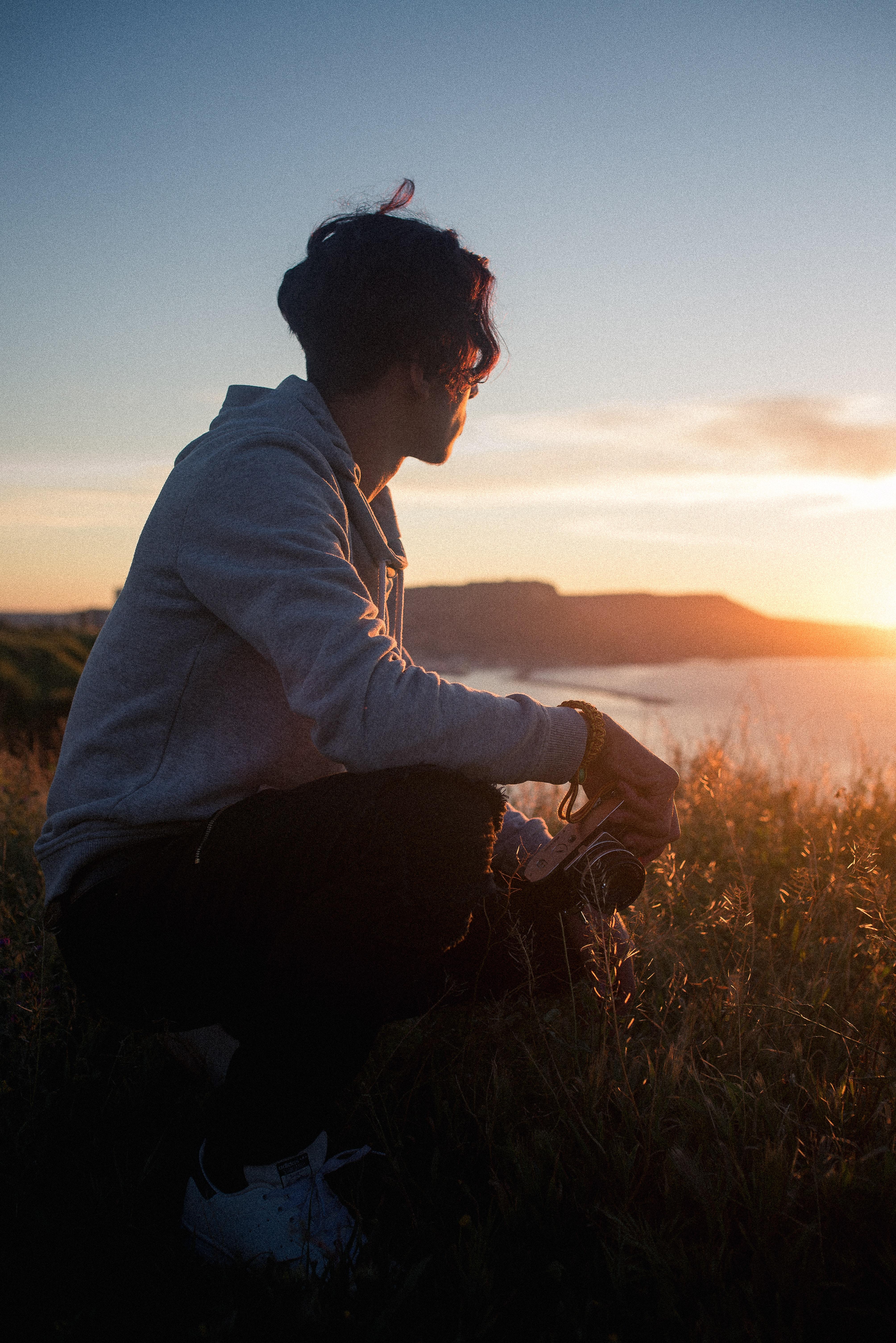 man sitting on rock while holding camera