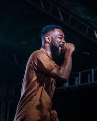 man singing on stage white wearing brown crew-neck shirt