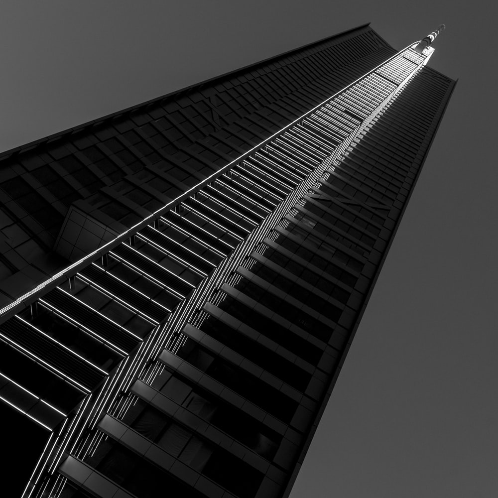 grayscale photography of concrete high-rise building