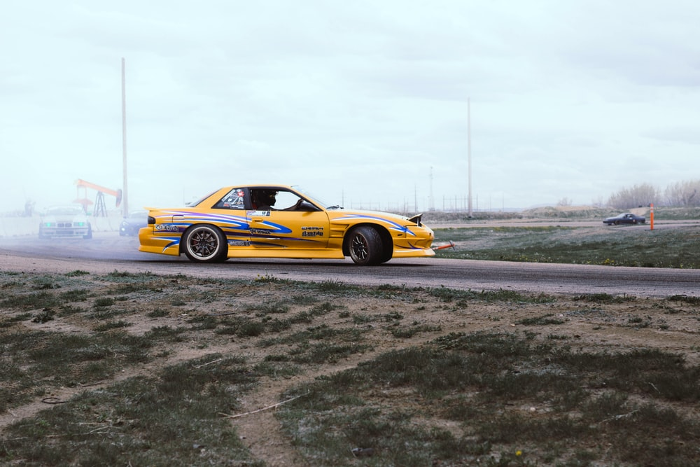 yellow and blue coupe drifts on black asphalt road during daytime