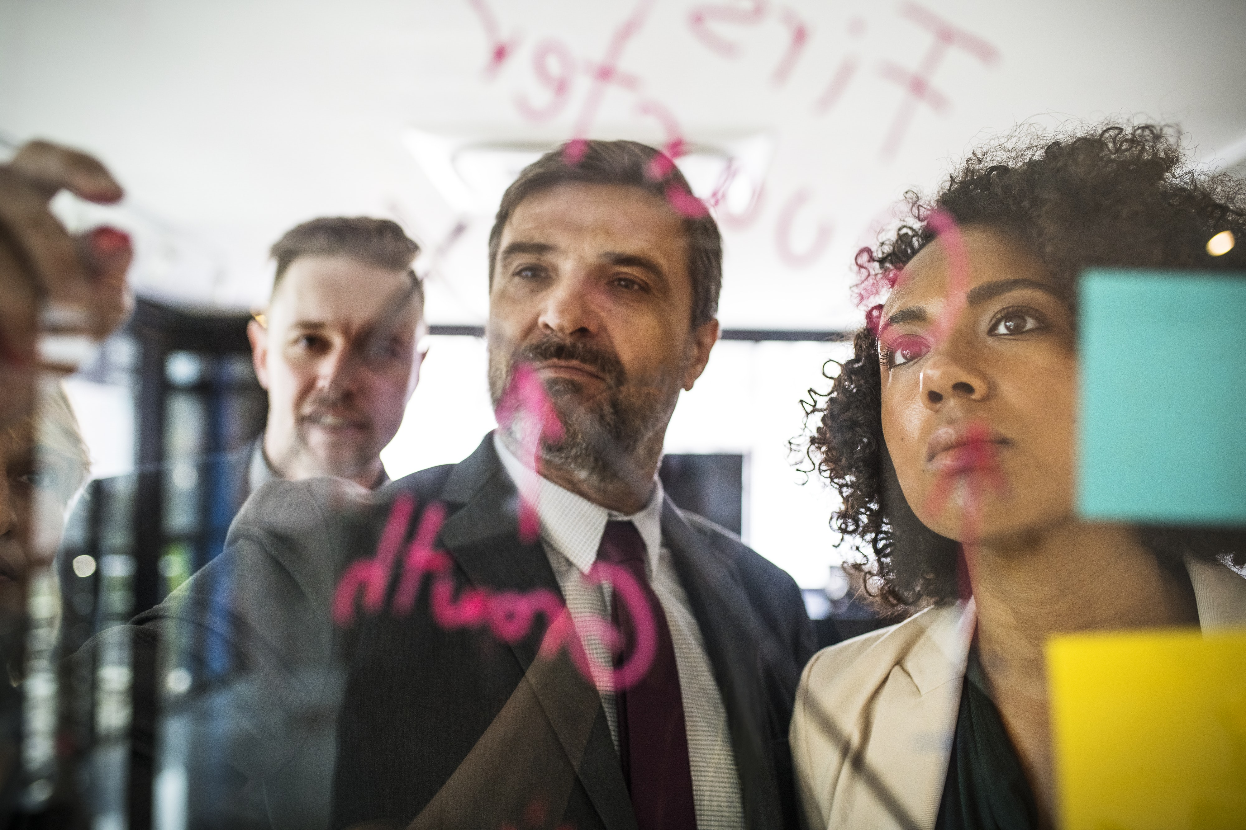 two men and one woman sticking paper on glass board