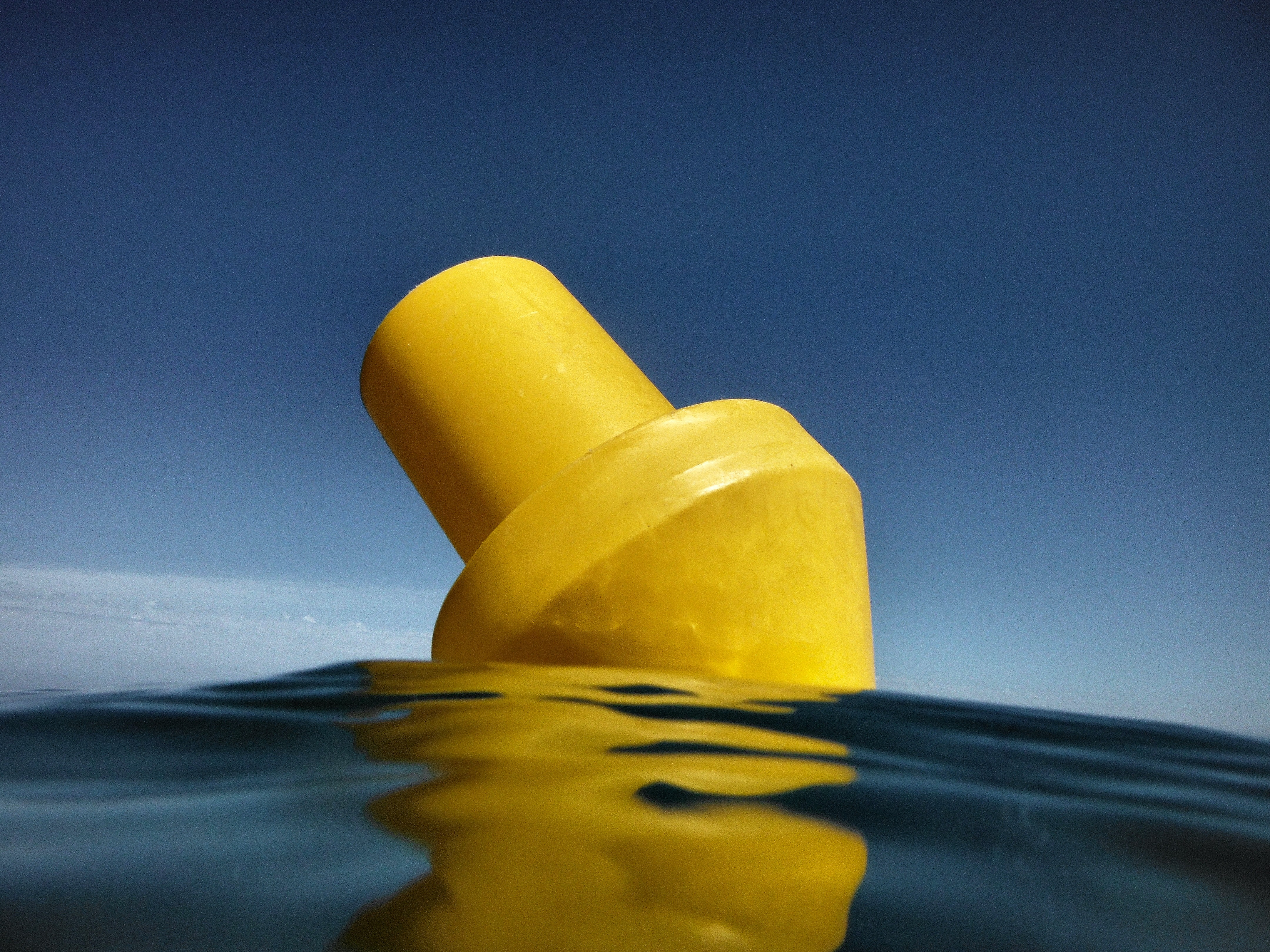 yellow plastic part floating on body of water during daytime