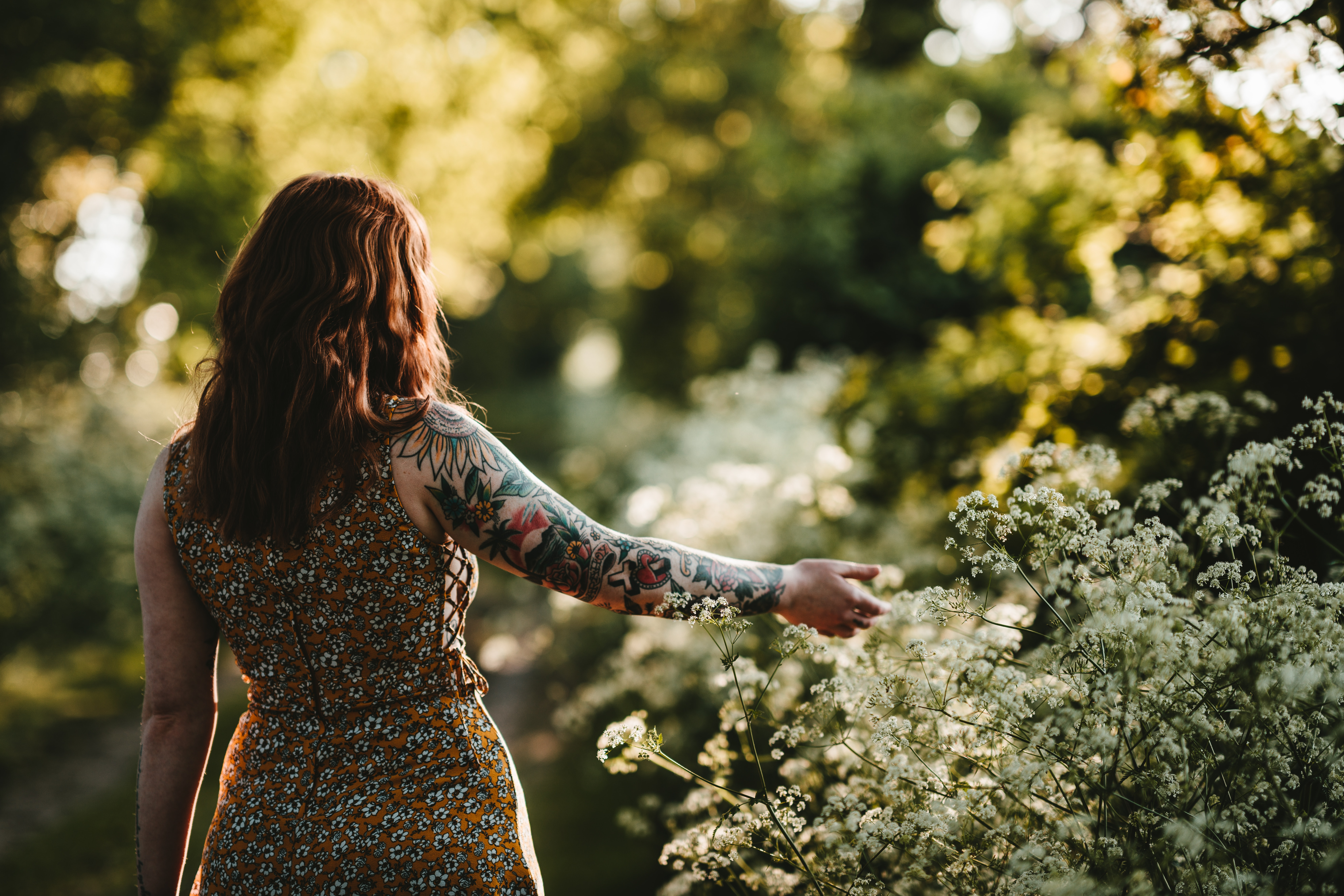 woman standing while holding white petaled flower selective focus photography