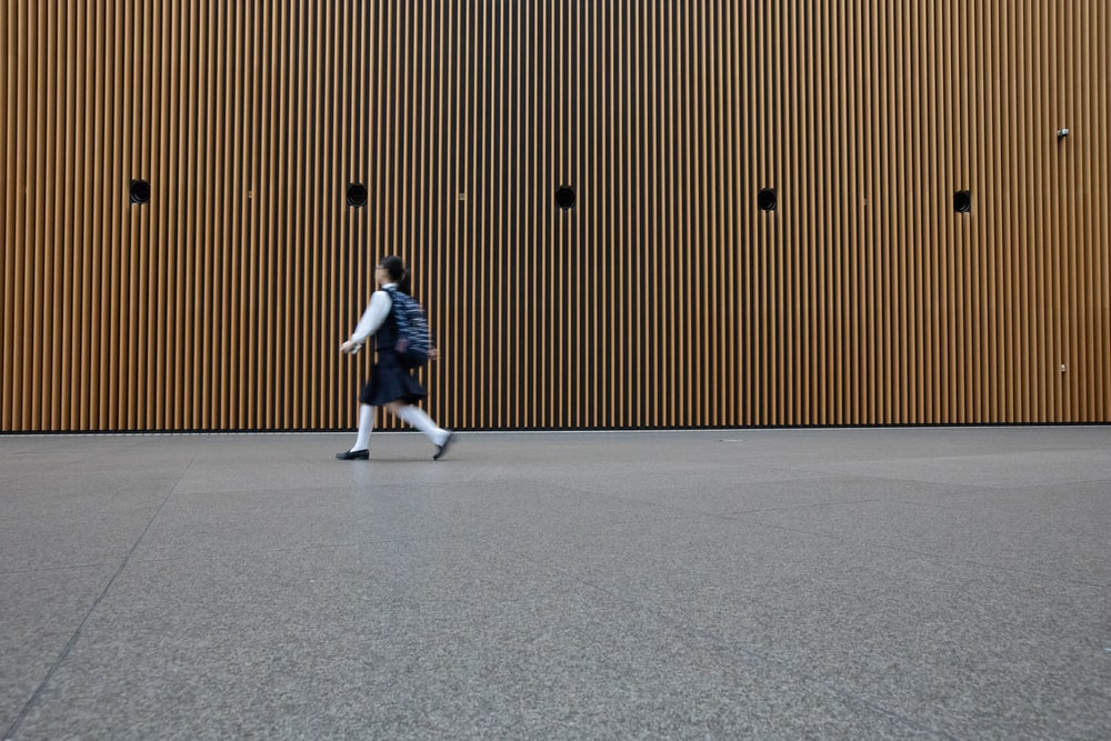 woman in uniform walkin on gray concrete pavement during daytime