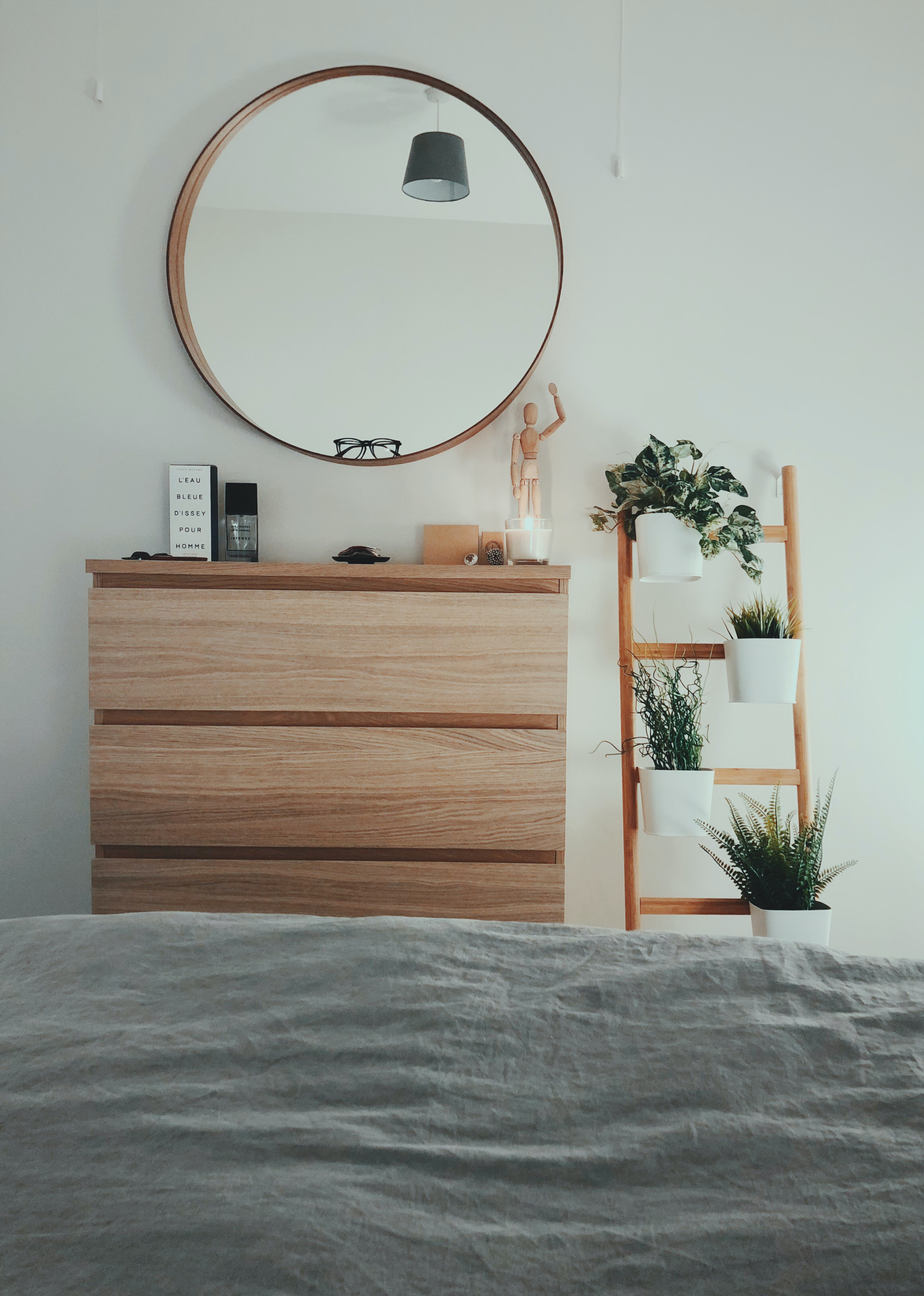 brown wooden 3-drawer chest with round brown wooden framed mirror in front of bed inside room