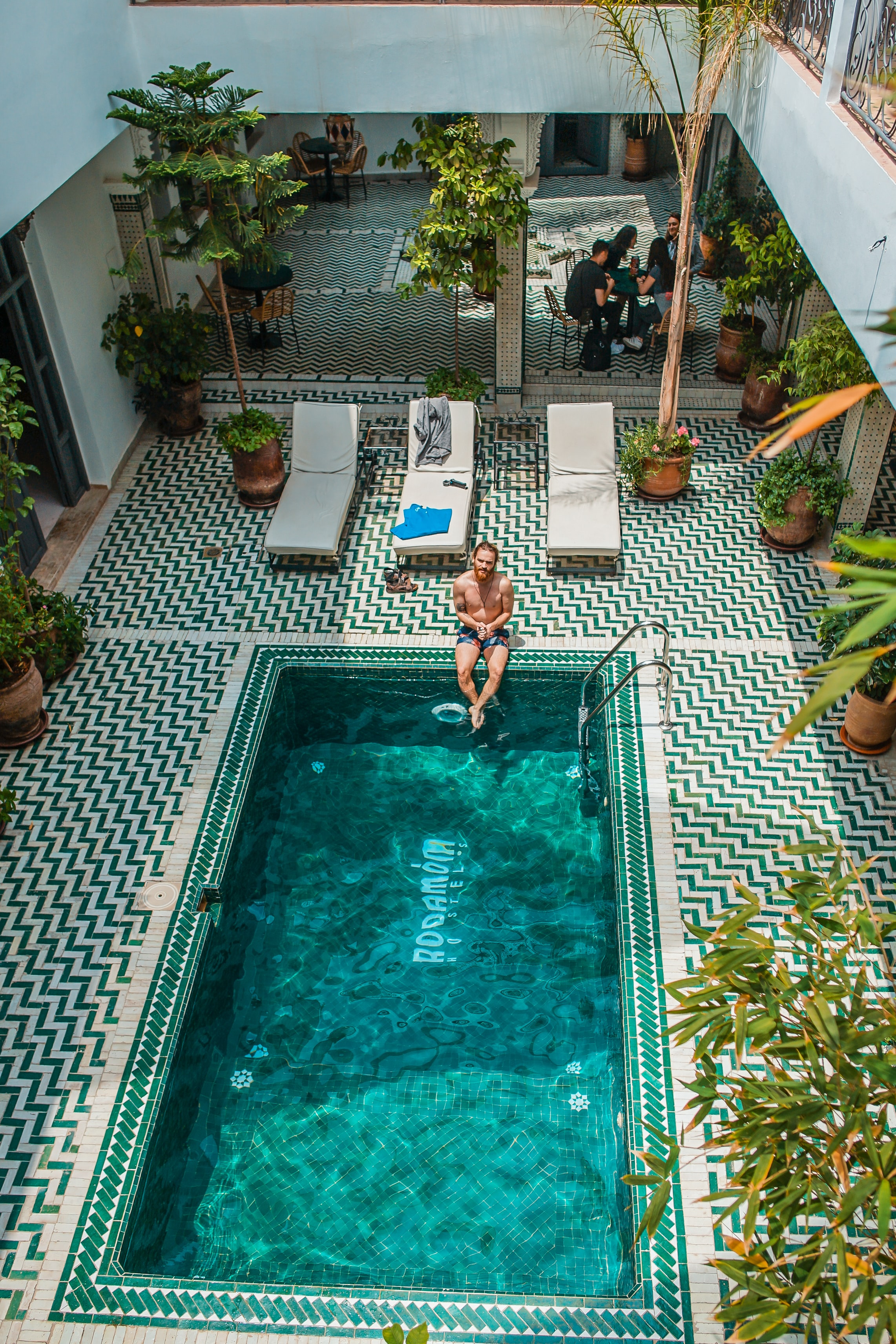 person sitting beside pool during daytime