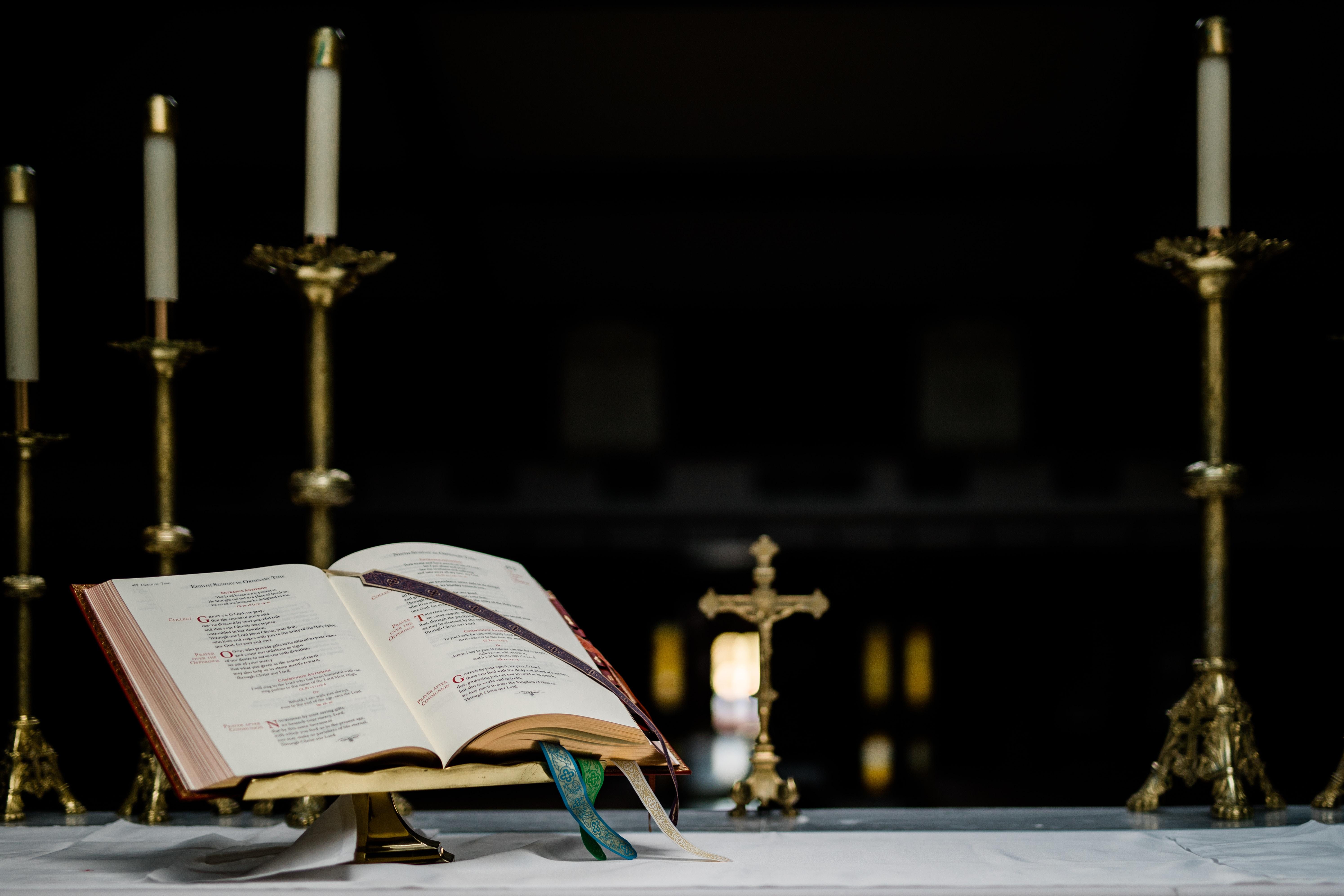 opened book near gold-colored crucifix