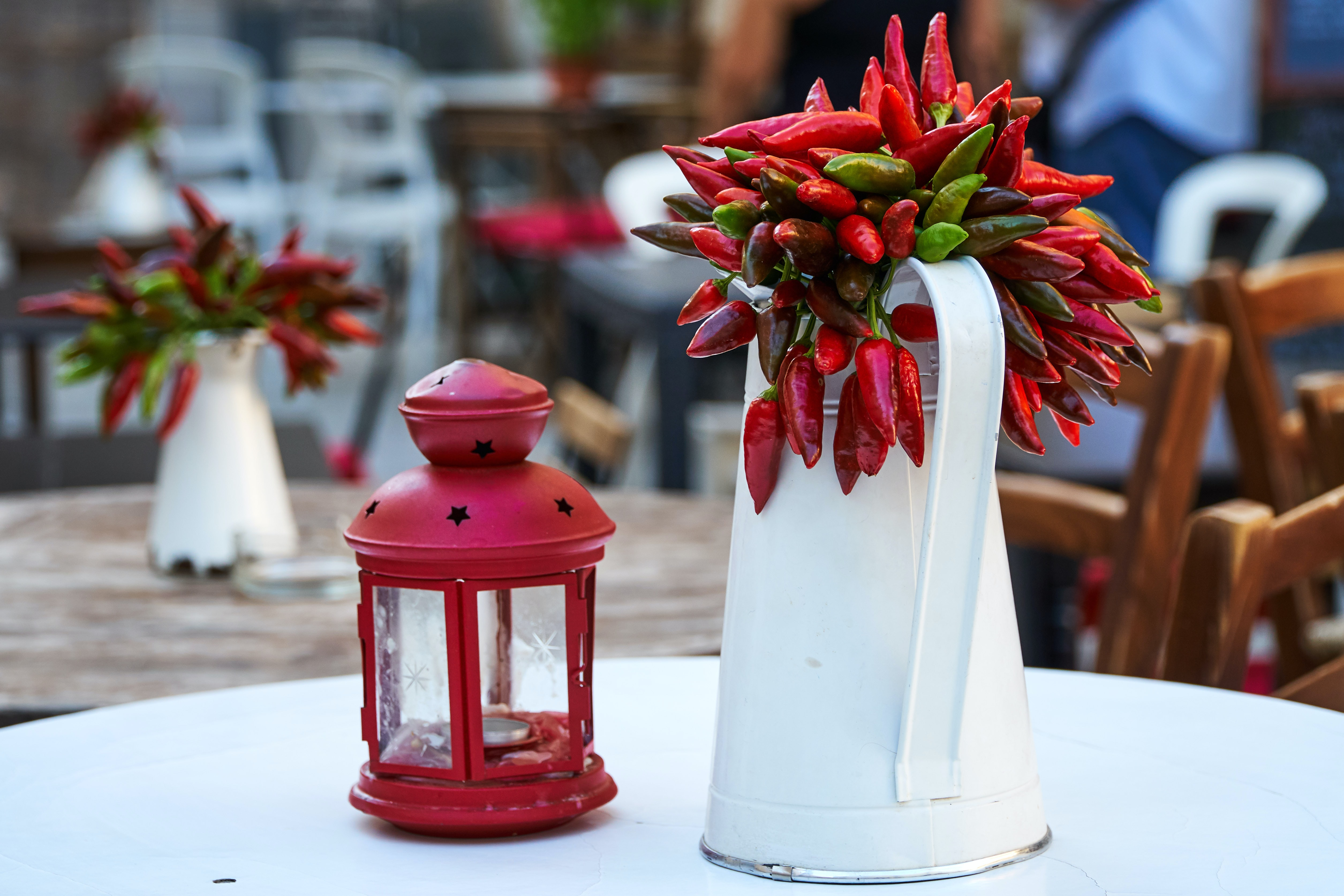 white pitcher beside red candle lantern