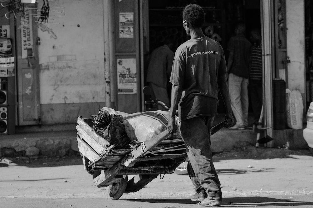 grey scale photo of man pushing cart