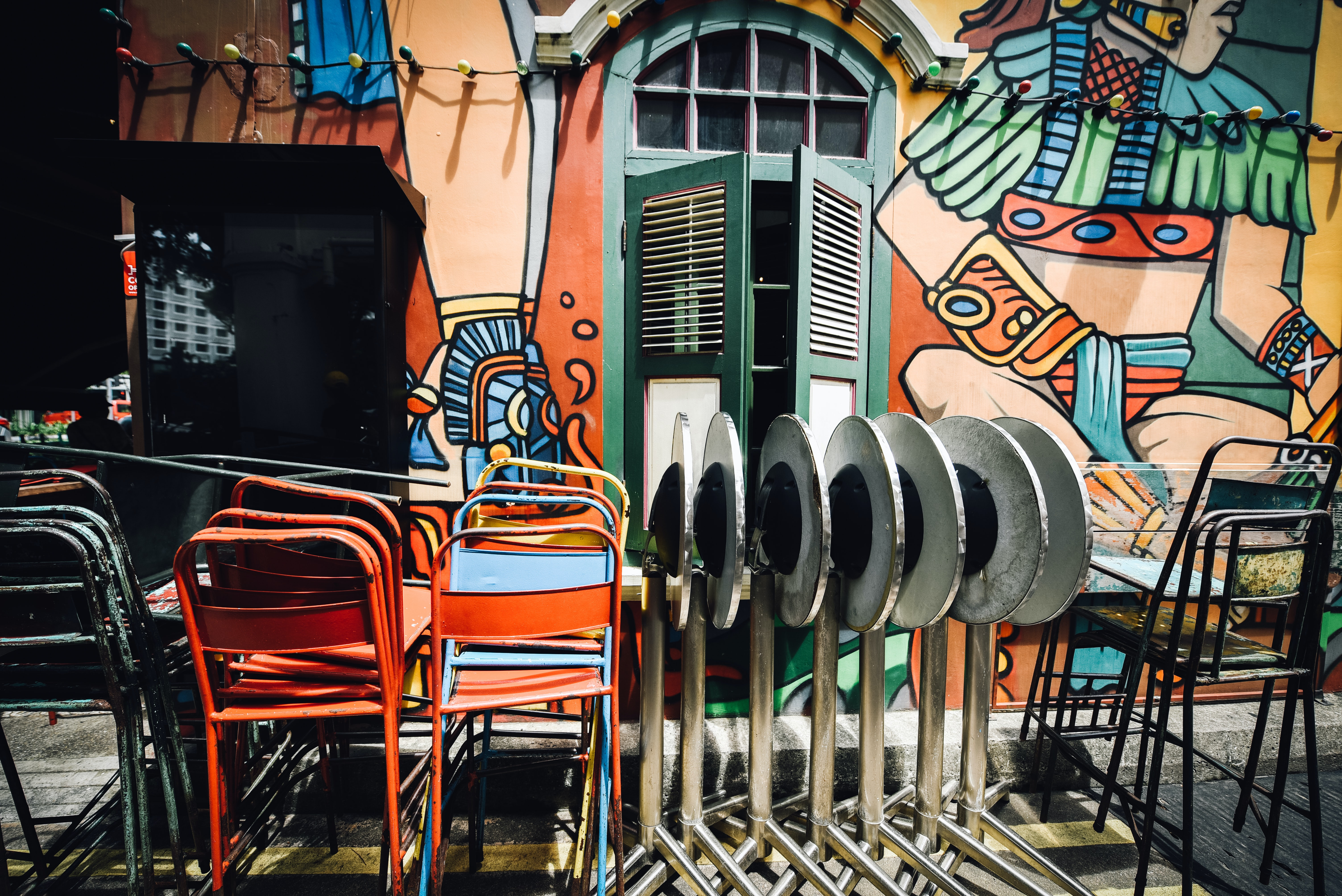 assorted-color metal chairs outside building wall art