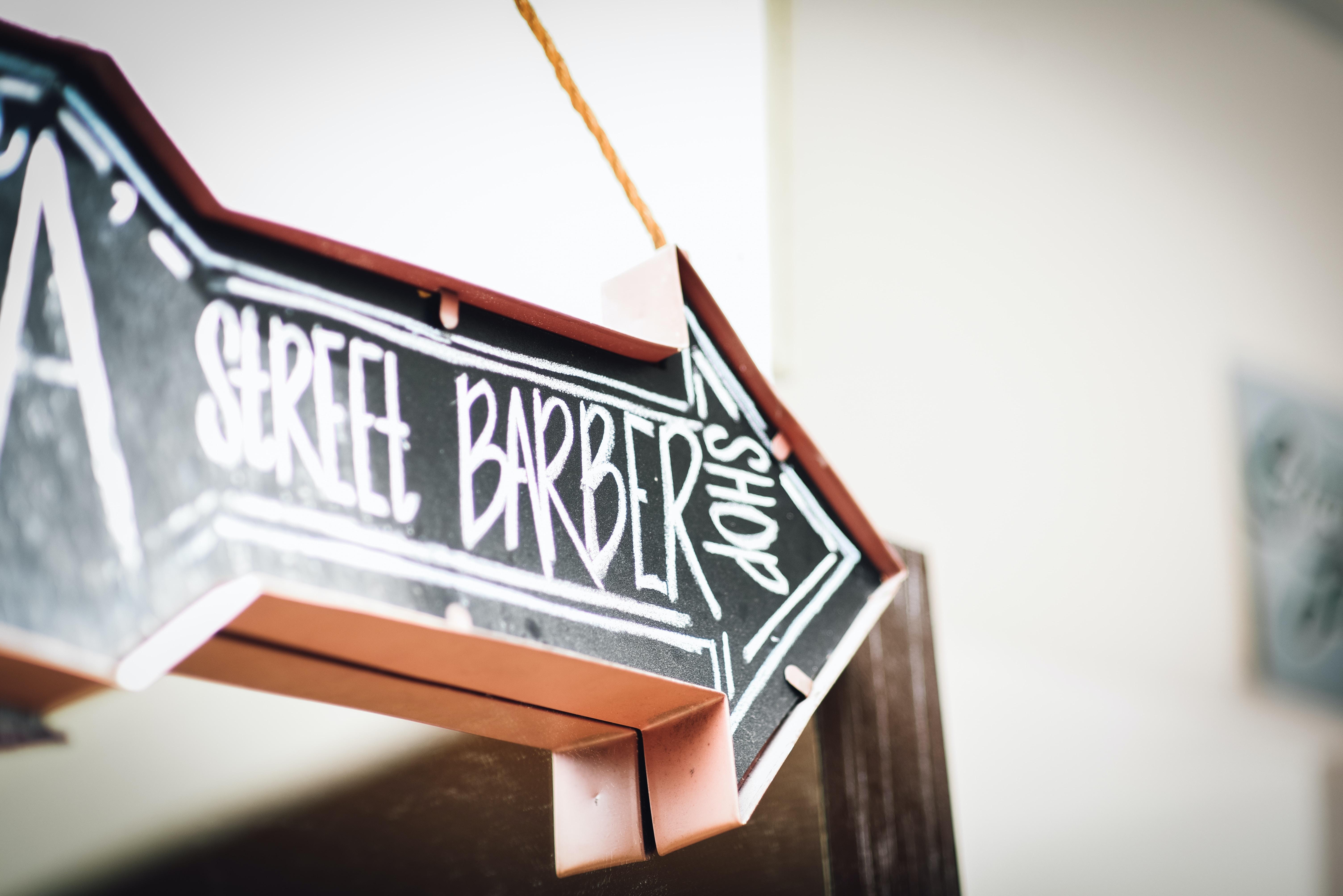 black and white Street Barbershop arrow signage