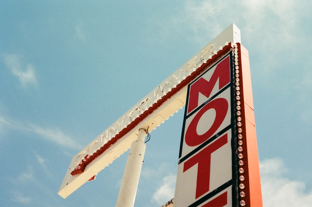 white and red Motel sign under blue sky