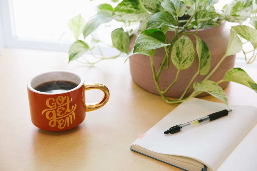 black retractable pen on opened book beside red and white go get'em-printed coffee cup