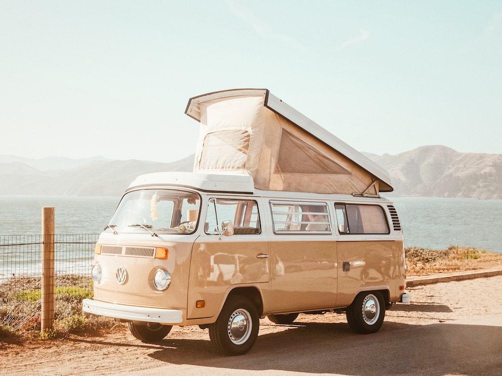 brown Volkswagen T1 van near body of water at daytime