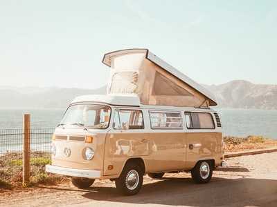 brown volkswagen t1 van near body of water at daytime retro zoom background