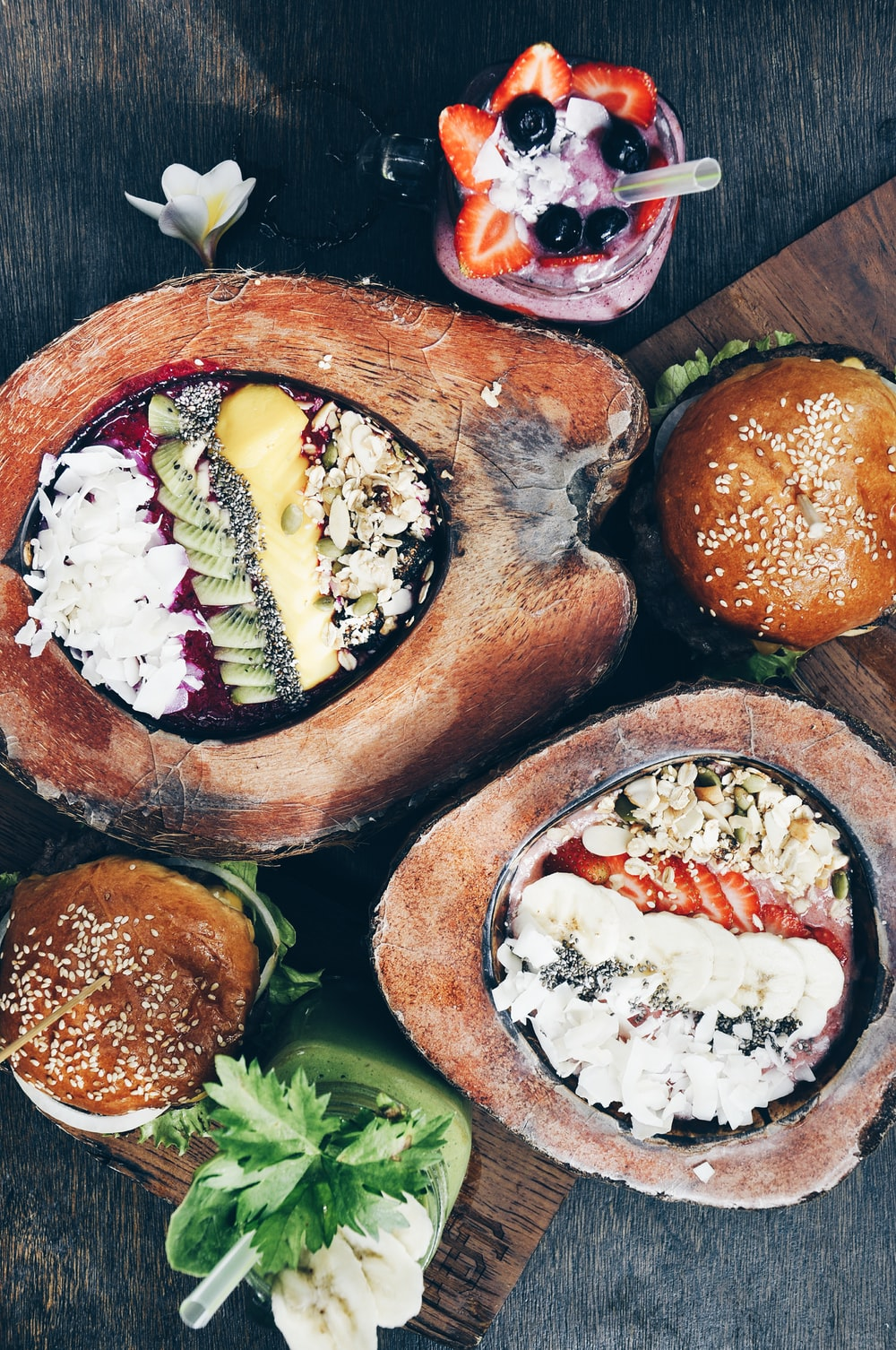 flat-lay of hamburger, fruit salad, and strawberry shake