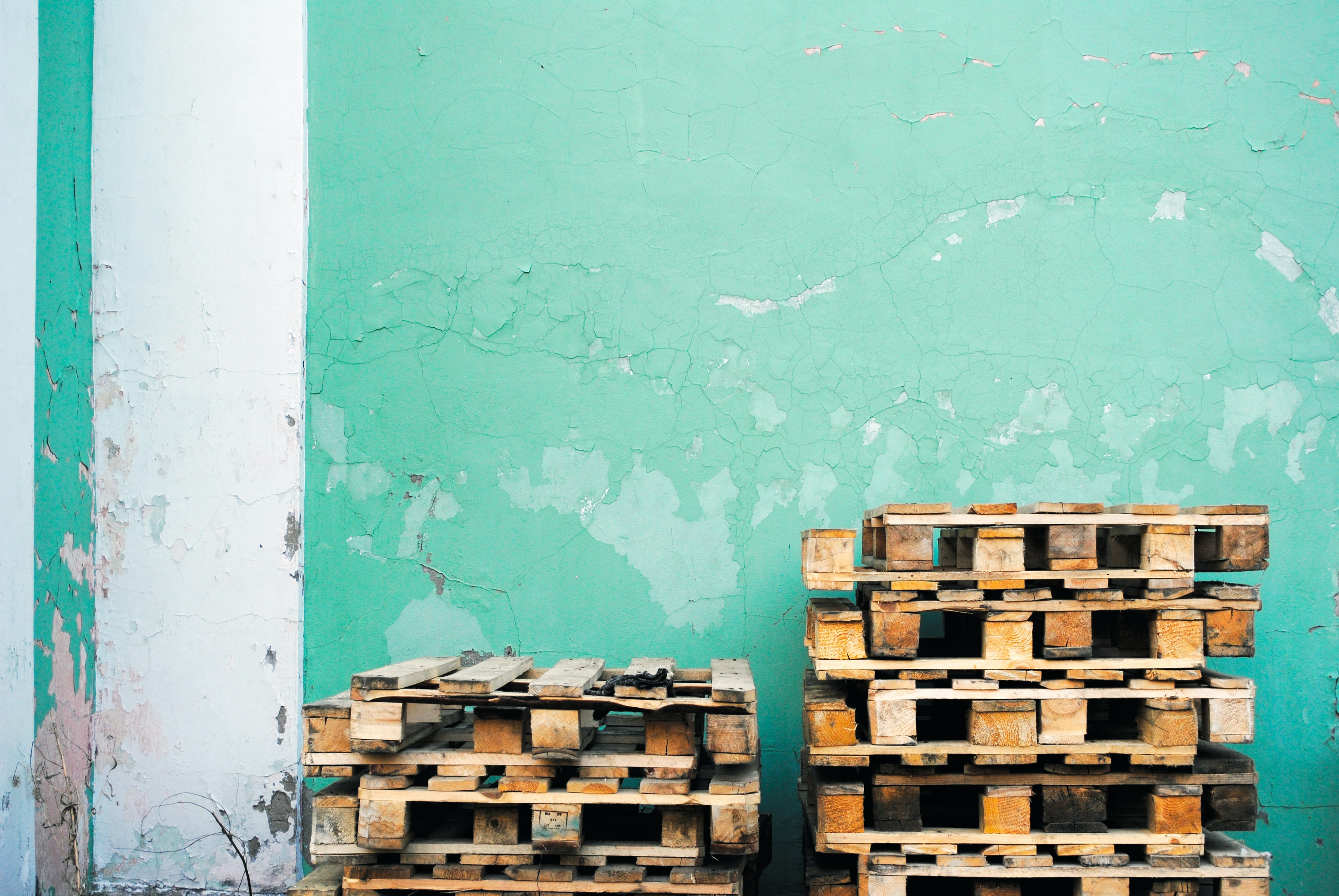 pile of brown wooden pallet lot near green wall