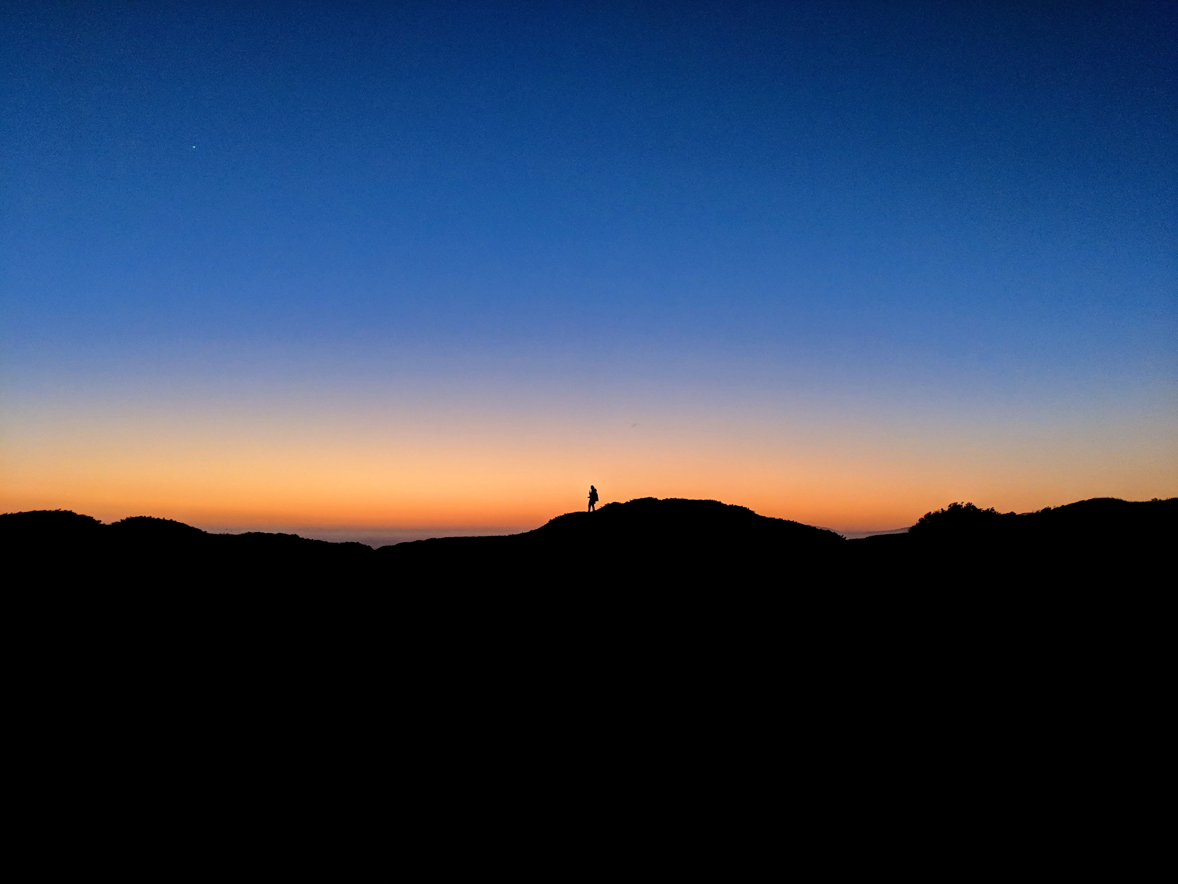 silhouette of person on mountain under clear blue sky