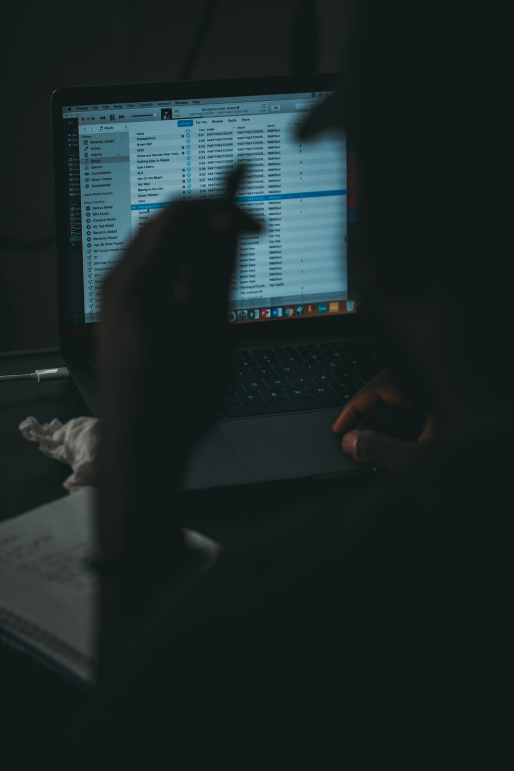 silhouette photography of man facing opened MacBook Pro with iTunes display