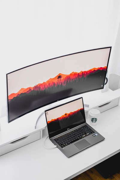 laptop computer beside curved monitor
