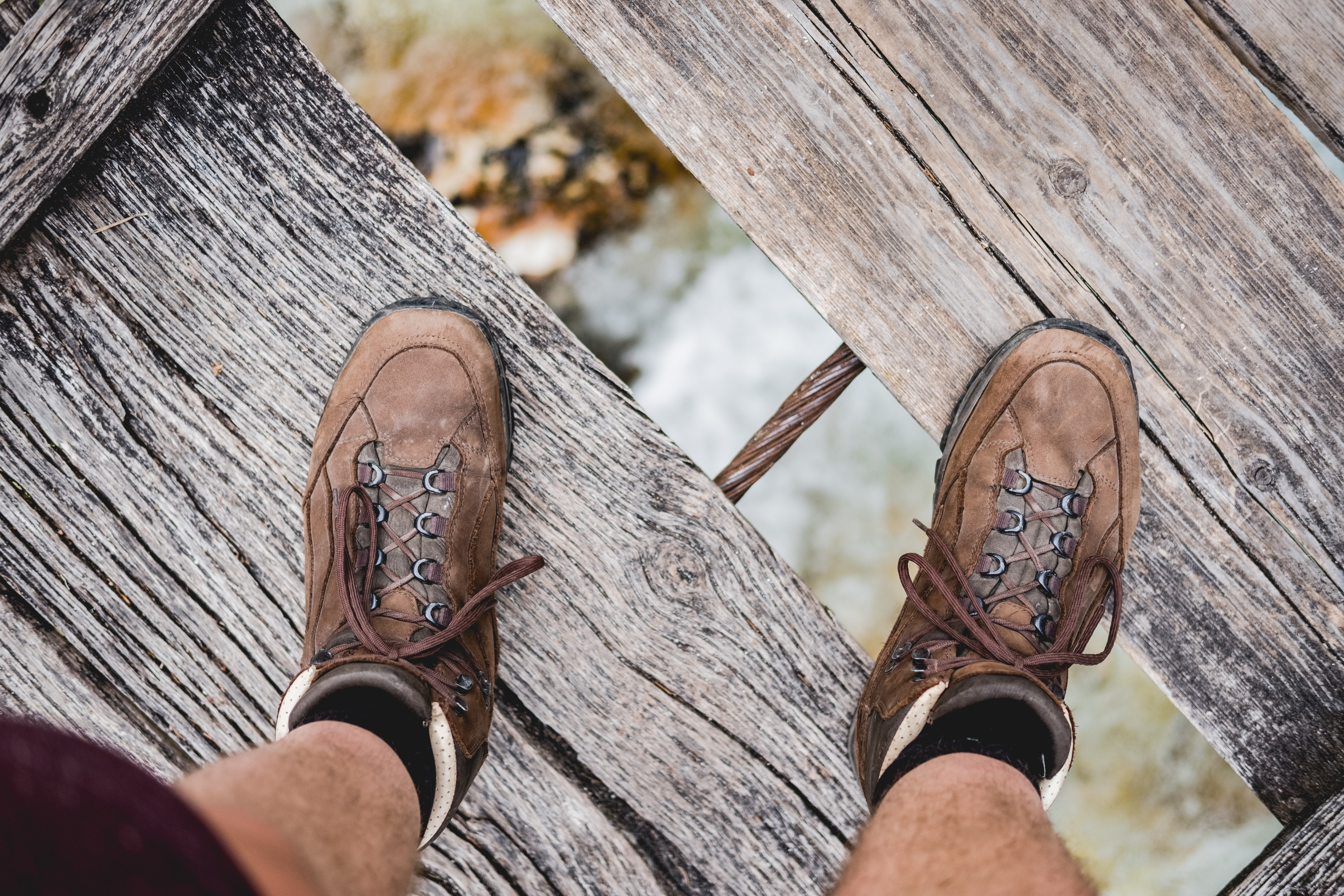 person wearing pair of brown shoes on wooden bridge under of river