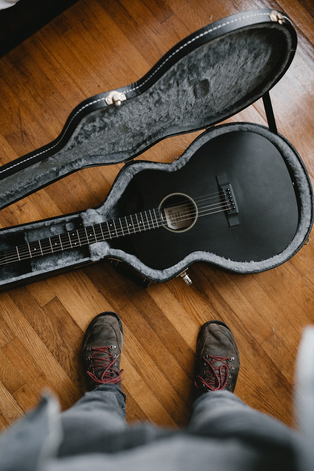 person taking picture of black classic guitar inside black and gray guitar case