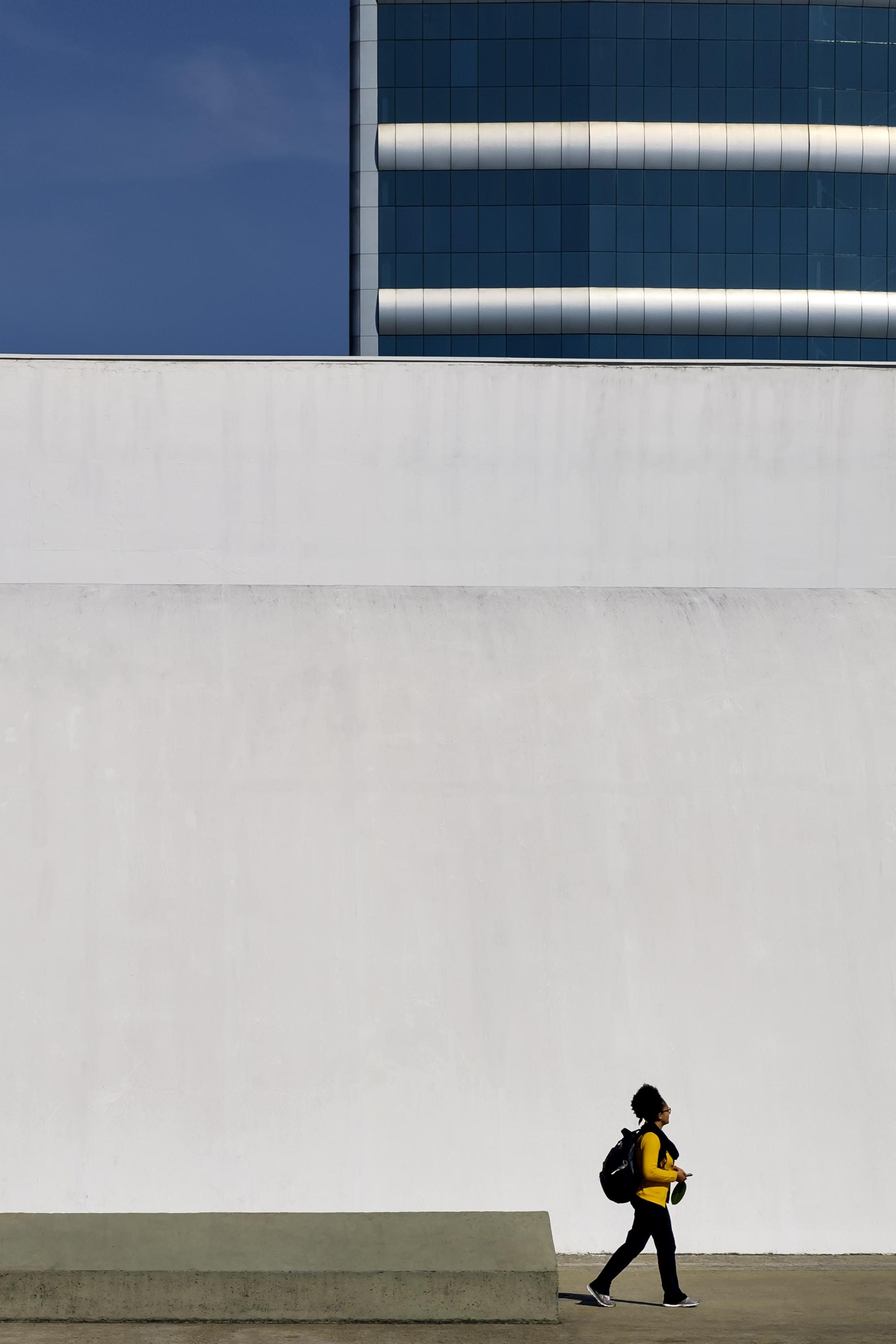 human in yellow long-sleeved T-shirt walking beside white concrete wall