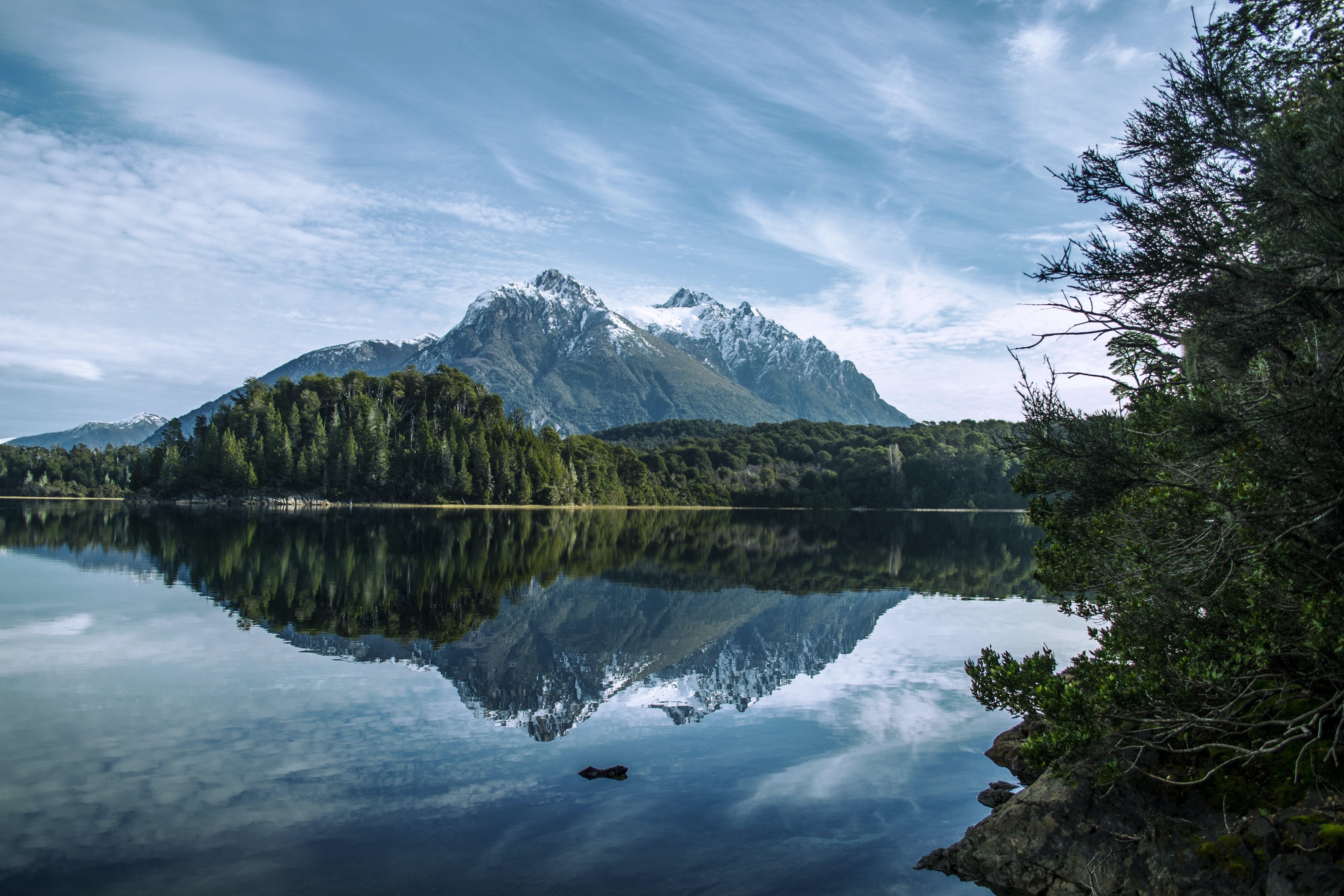 green trees and mountain reflecting on lake under cloudy sky