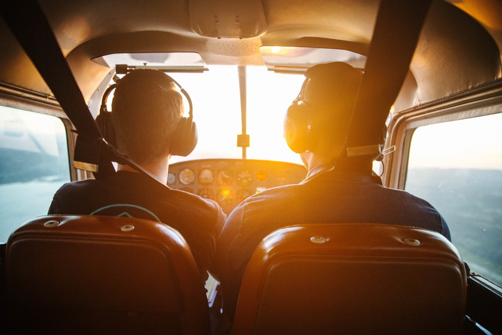 two men piloting plane during daytime