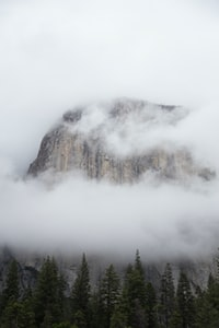 brown mountain surrounded by clouds