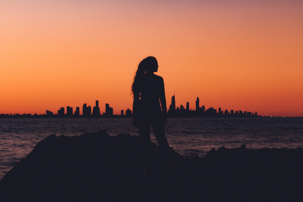 silhouette of woman near shoreline