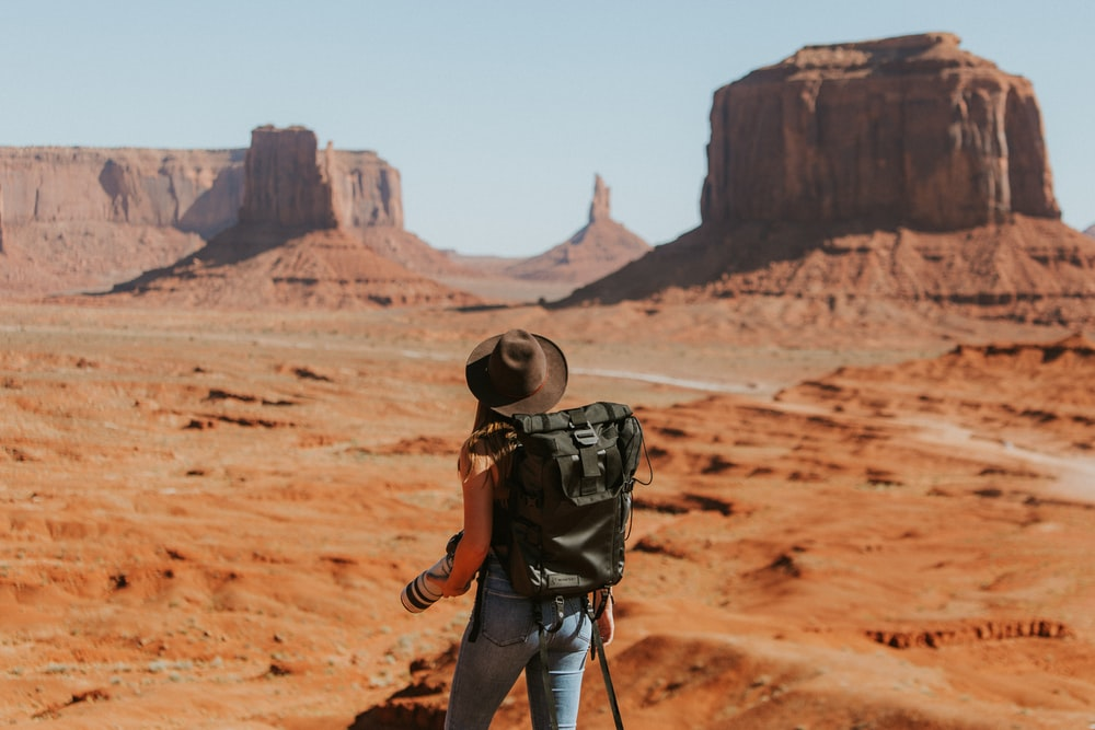 woman with black backpack standing on brown dessert