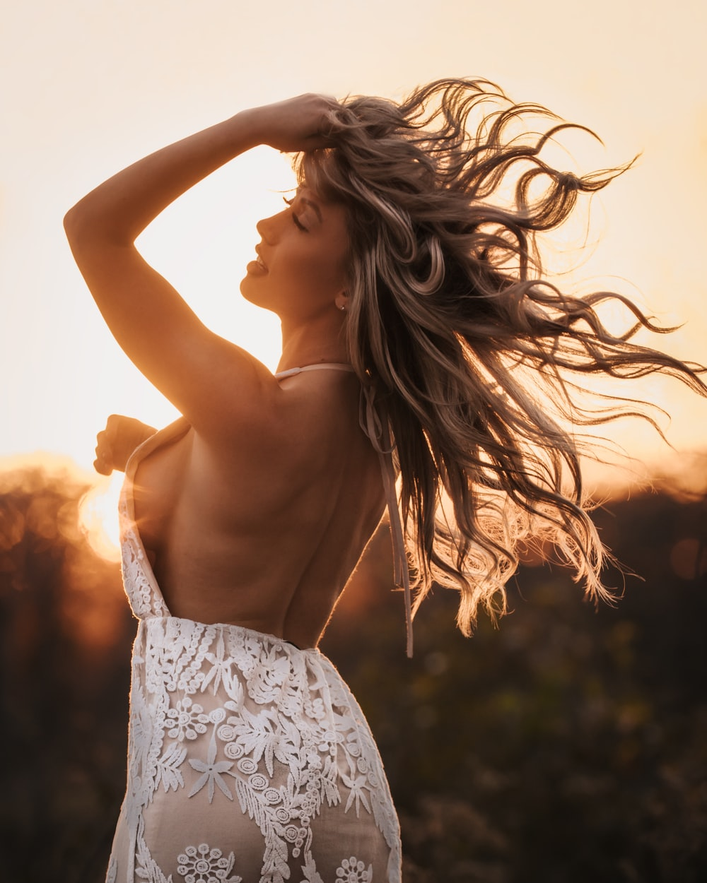 selective focus photography of woman in floral halter-neck open-back dress