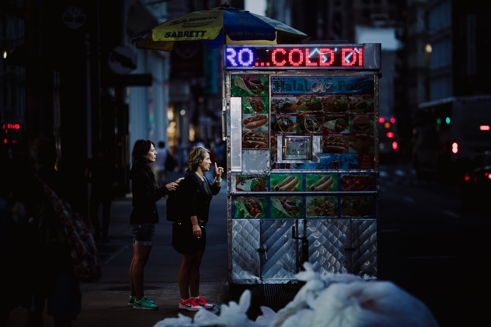two woman buying food on gray food stall at nighttime