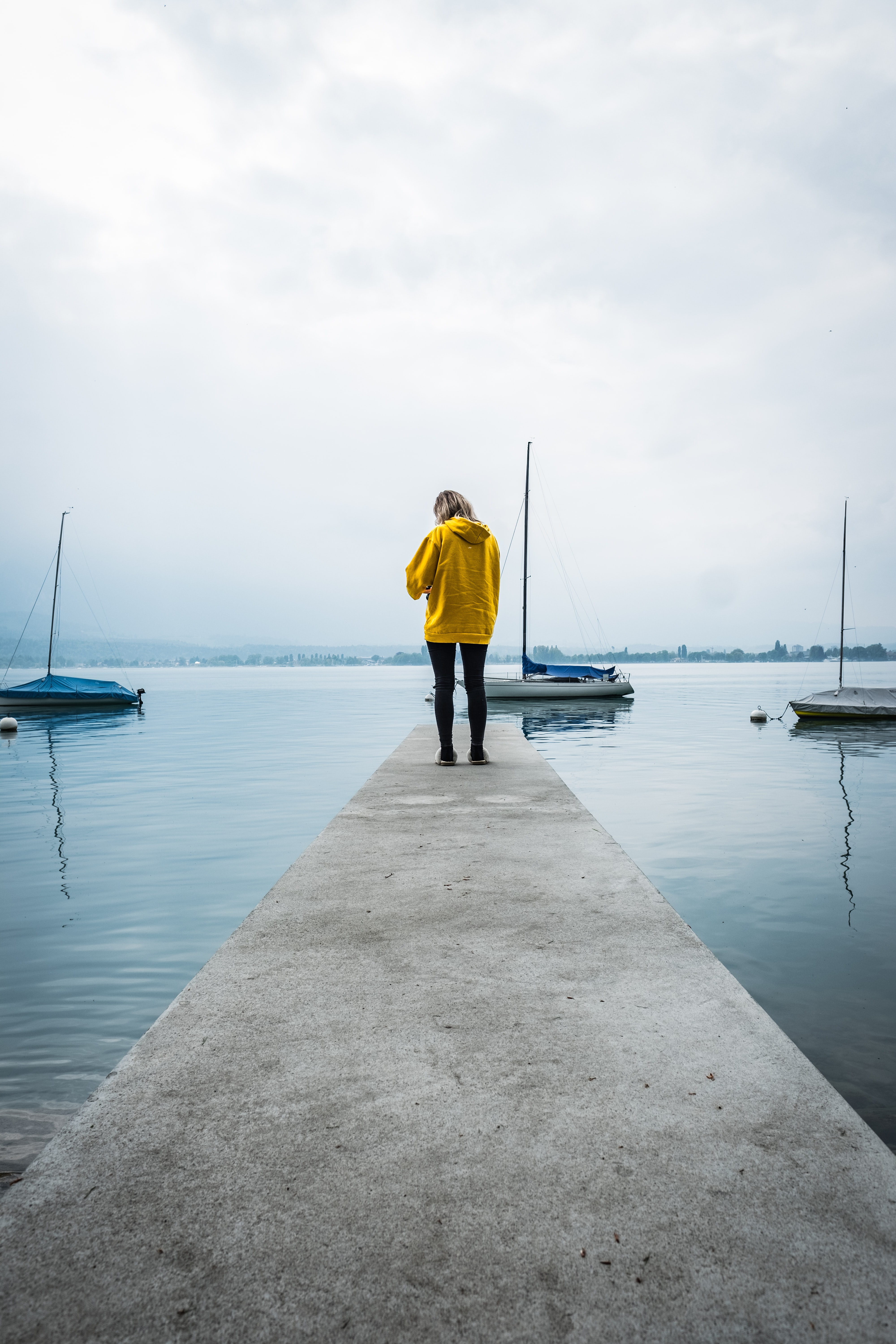 woman in yellow hoodie on concrete docking