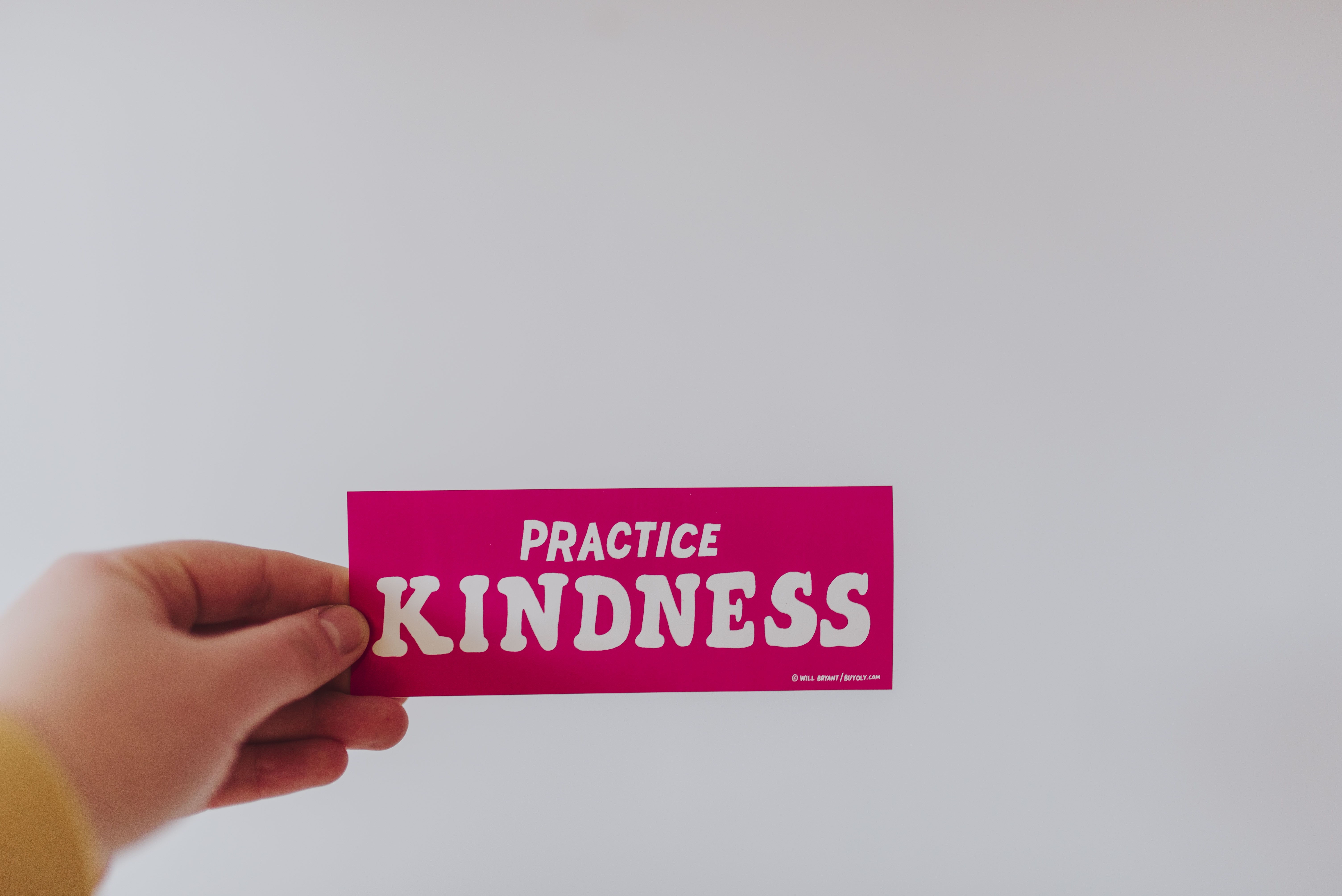 person holding red and white practice kindness sticker