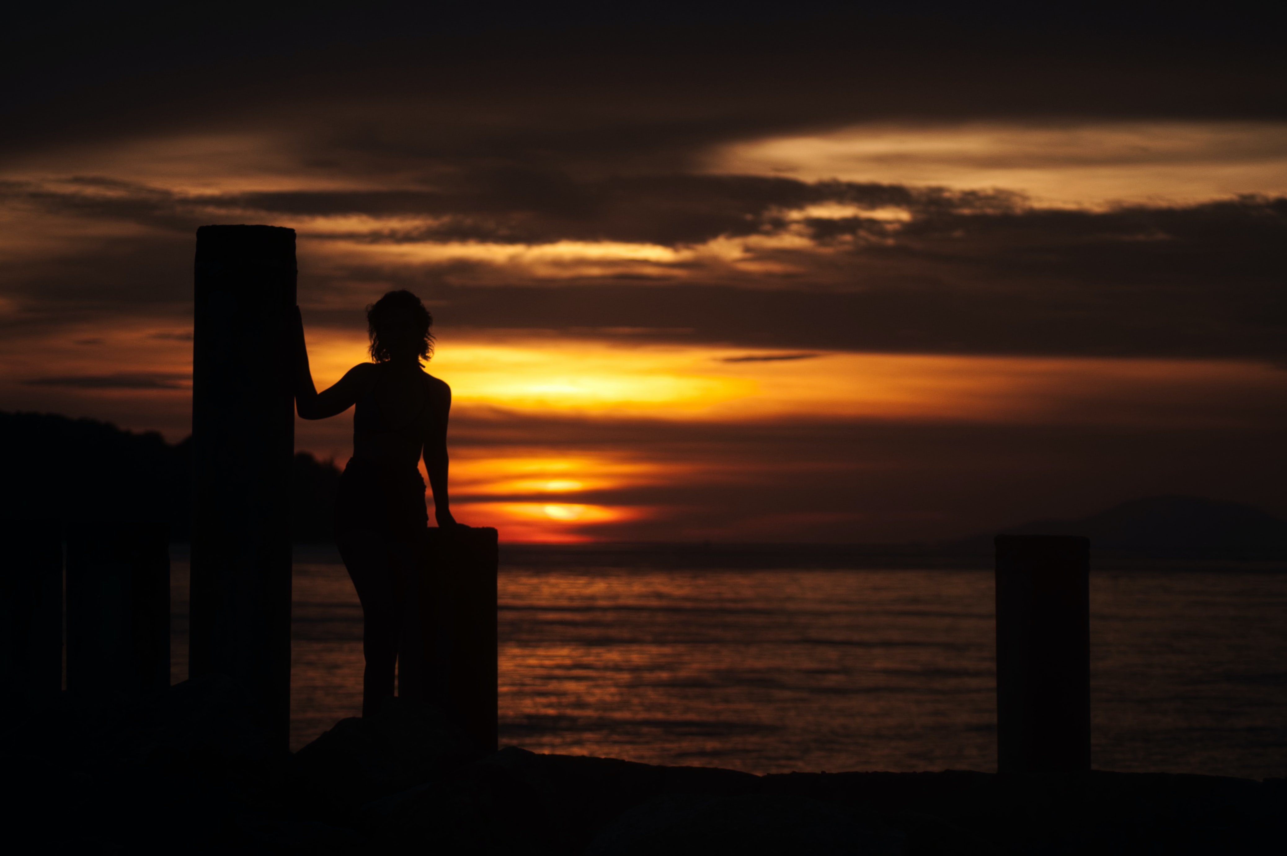 silhouette of woman on dock during orange sunset