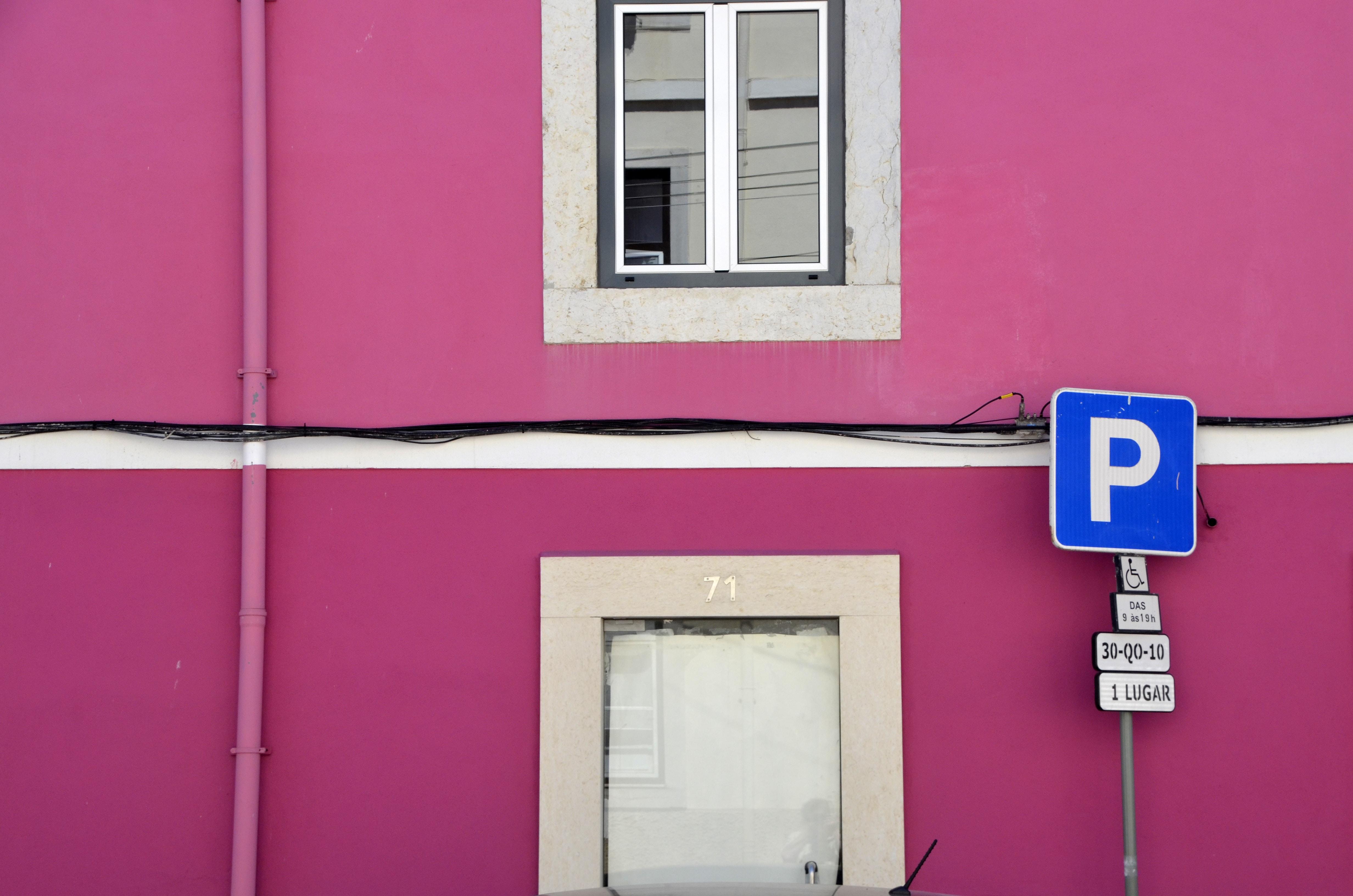 Parking signage near pink concrete building