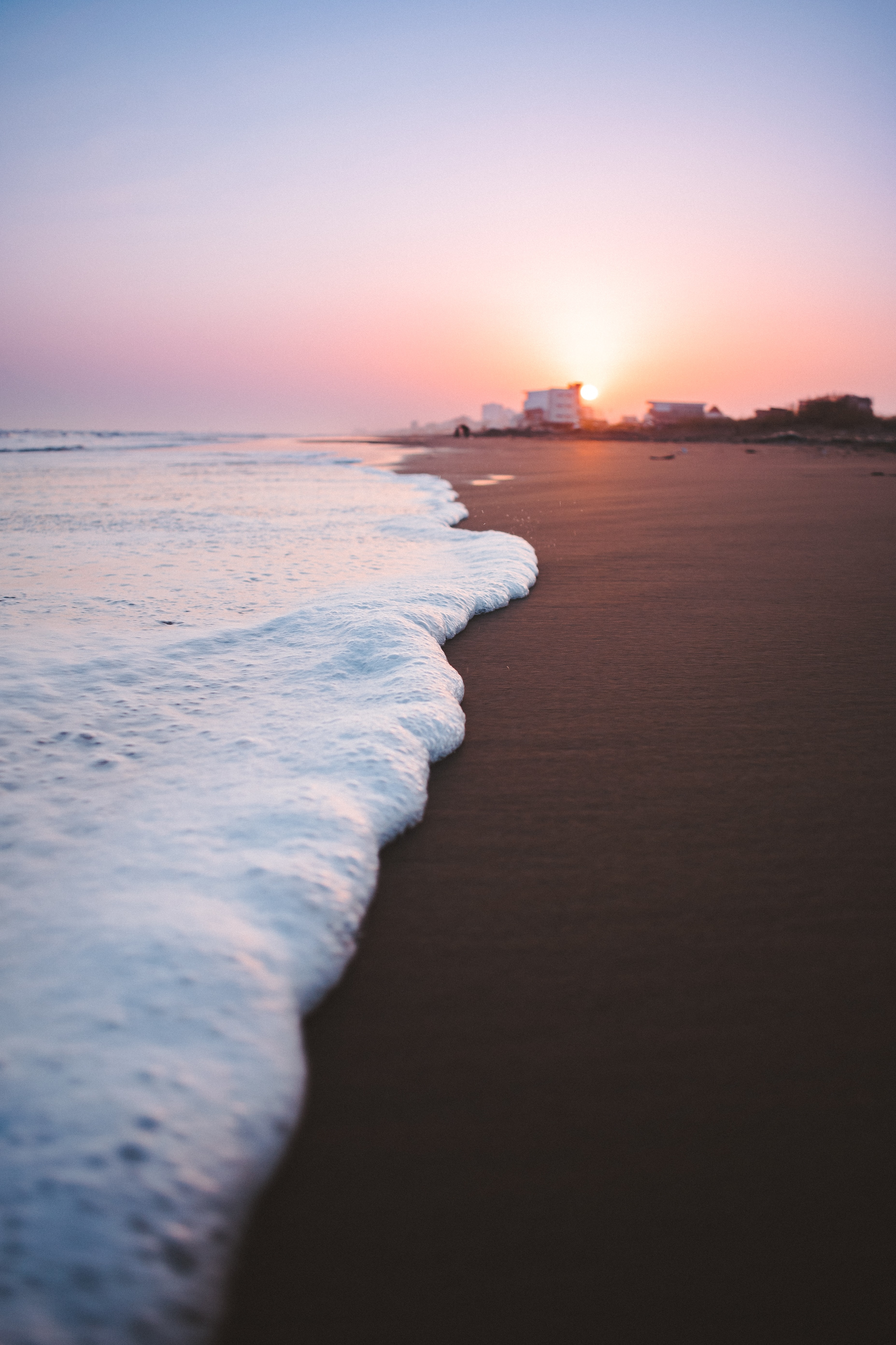 waves on brown sand closeup photography during sunset