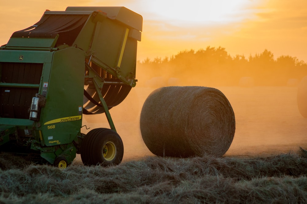 green heavy equipment and hay roll