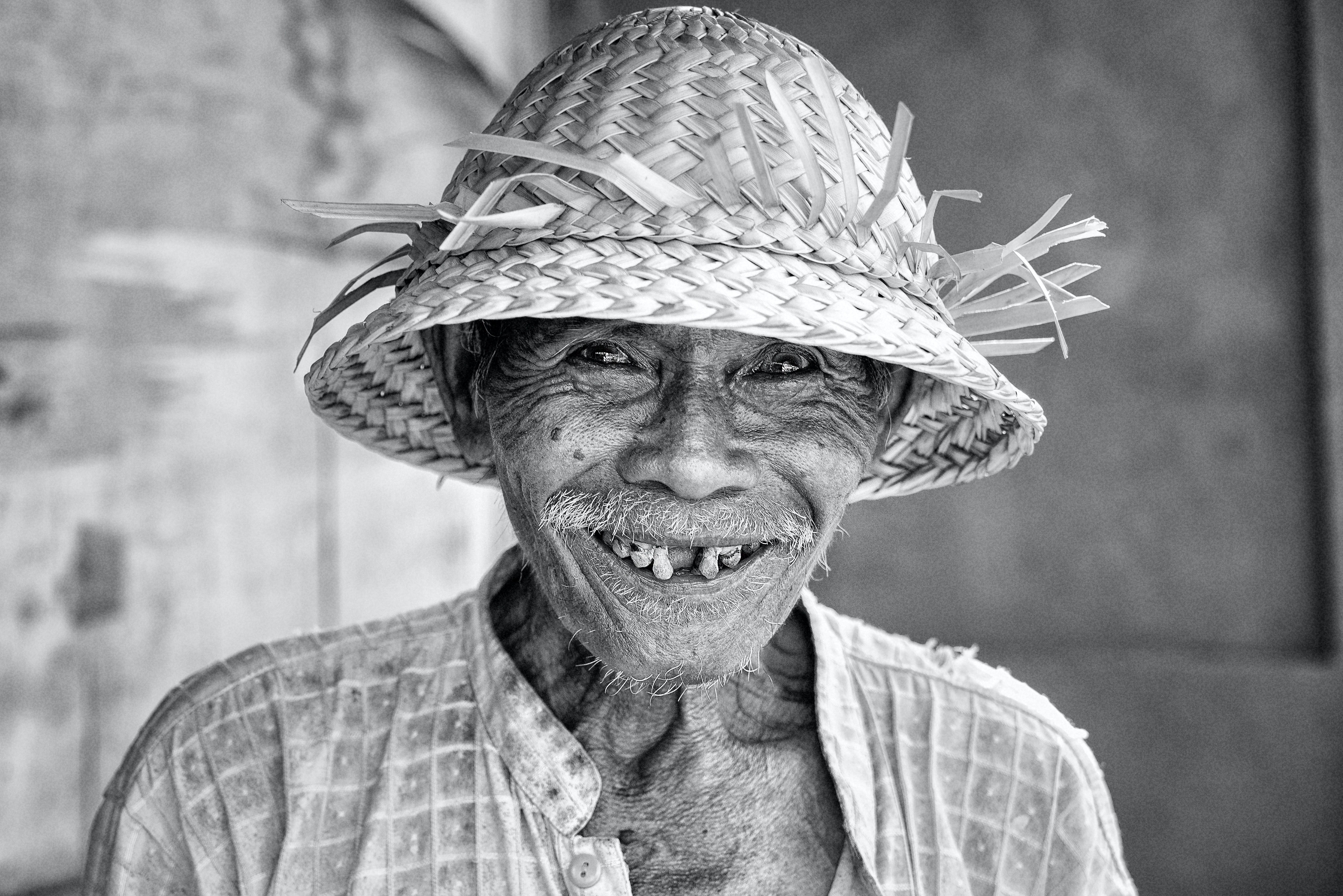 grayscale photo of man smiling wearing straw hat