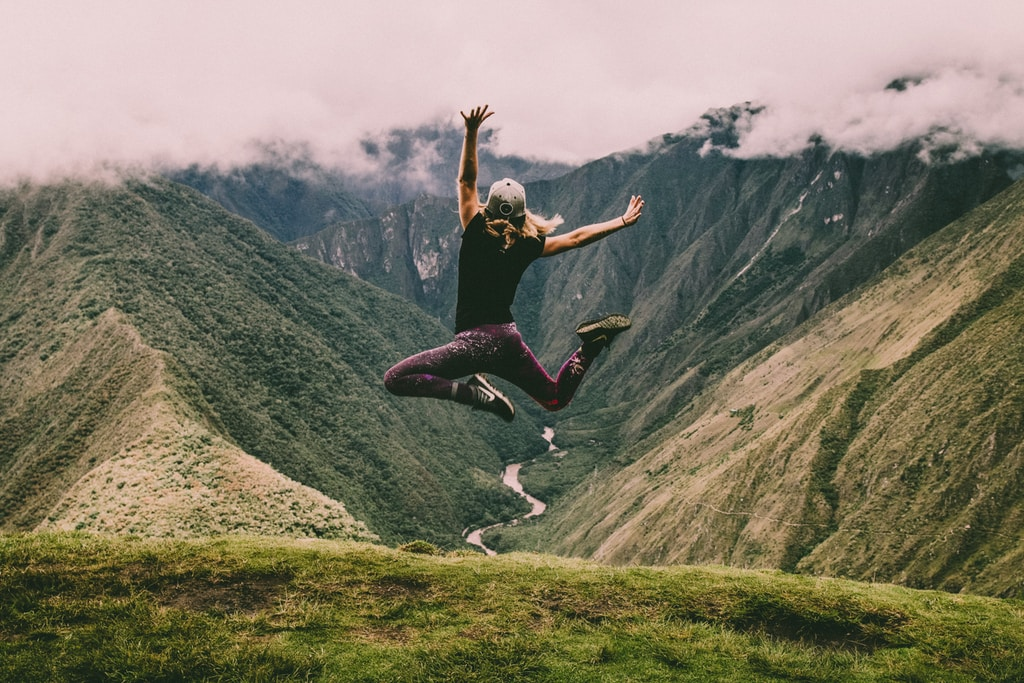 hiker jumping on green mountains