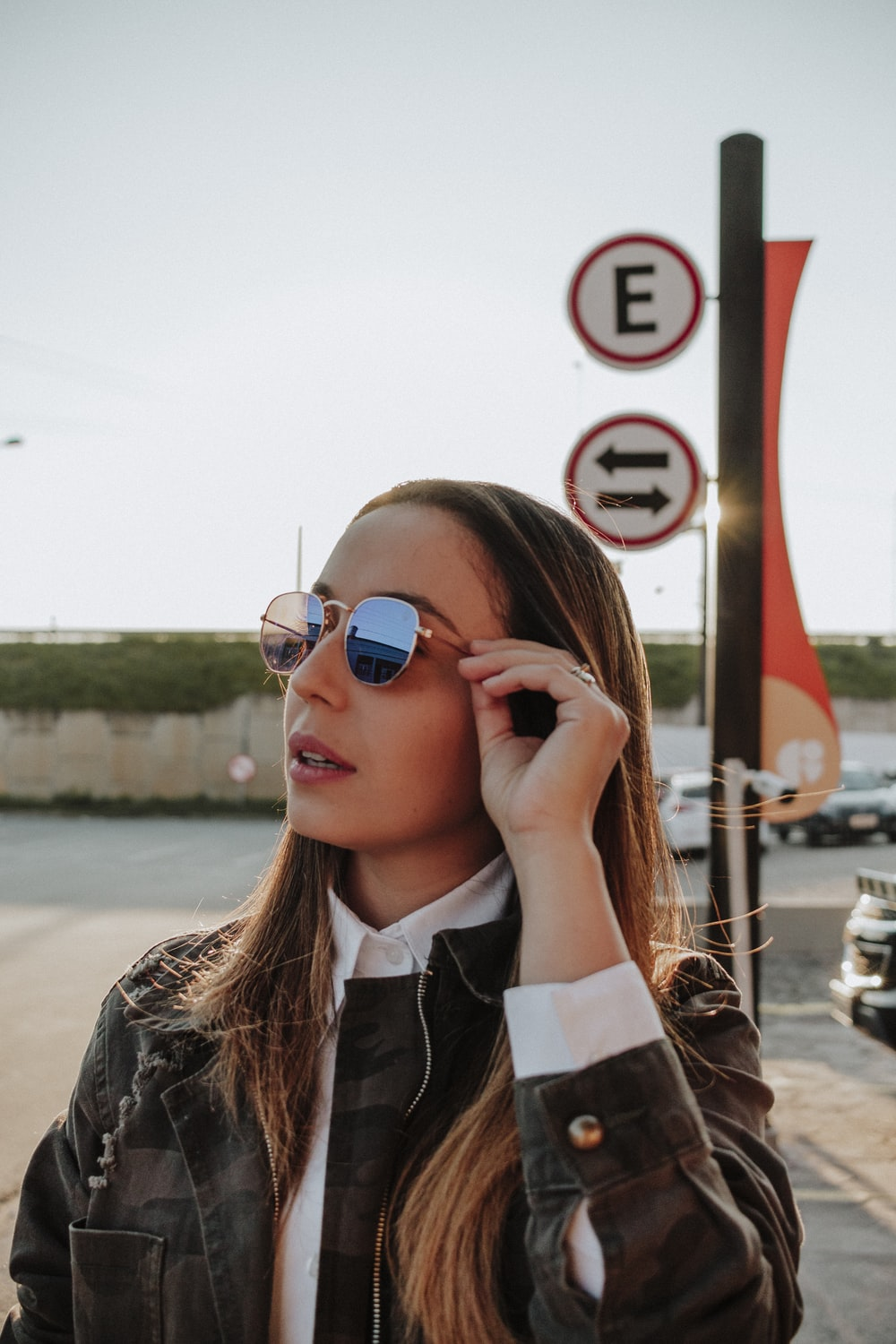 woman holding her sunglasses standing on parking lot during daytime