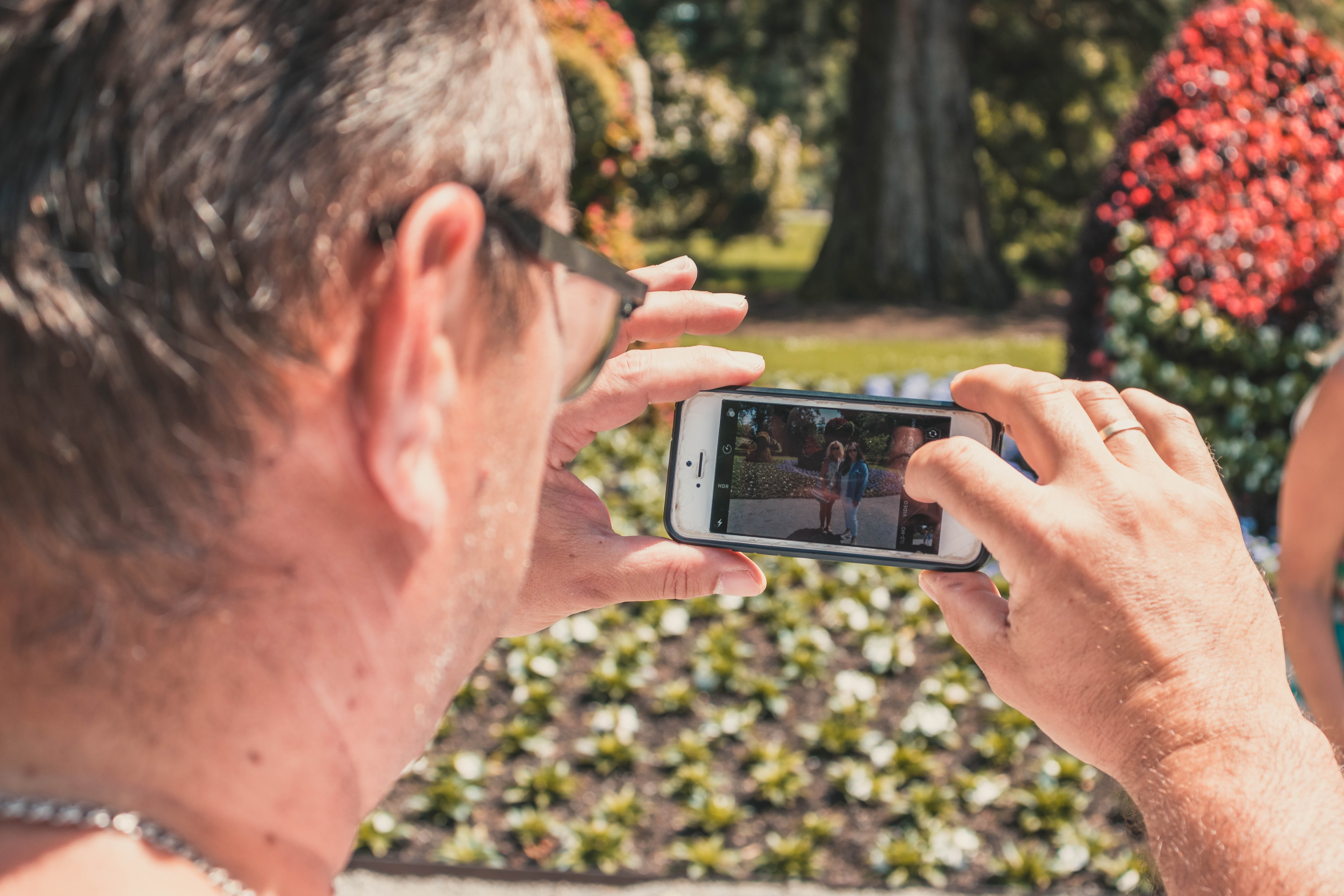 man holding white iPhone 5 taking picture of two woman standing during daytime