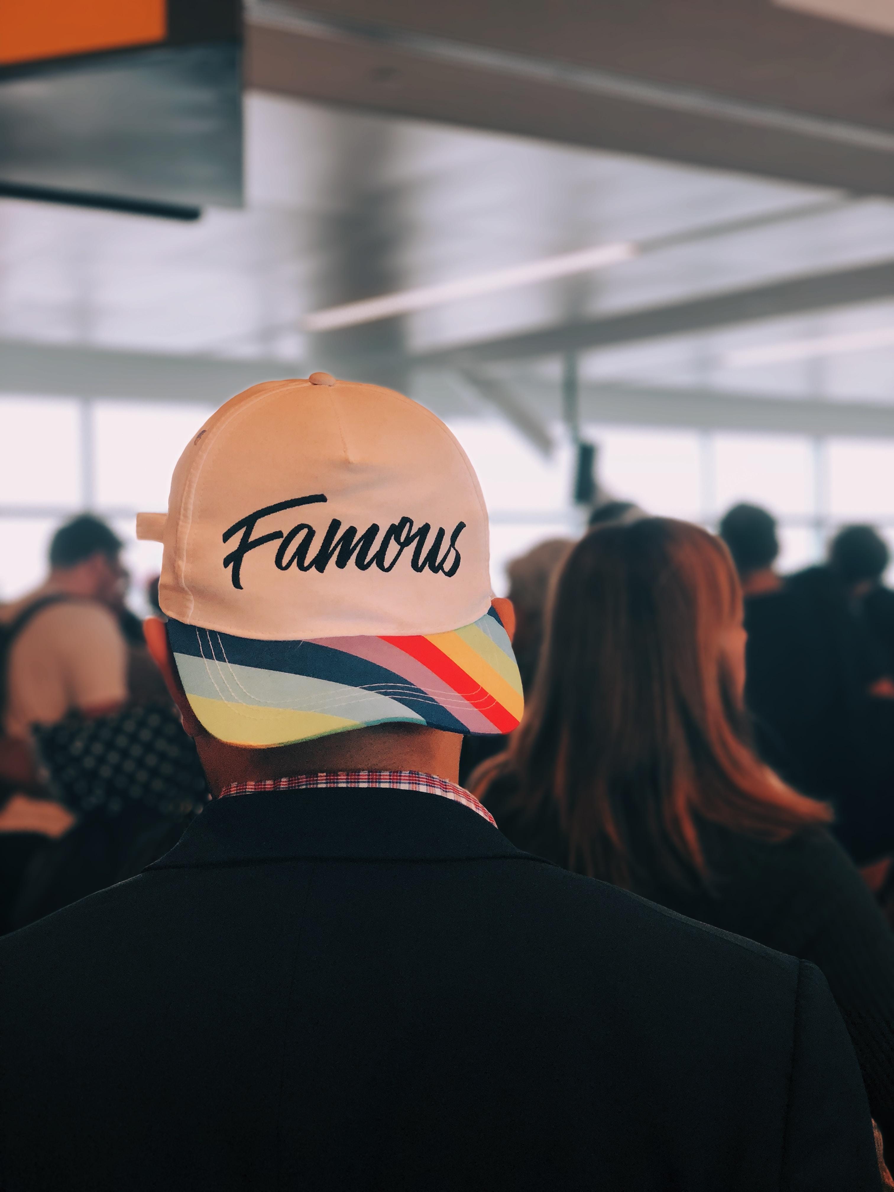 man wearing multicolored Famous cap