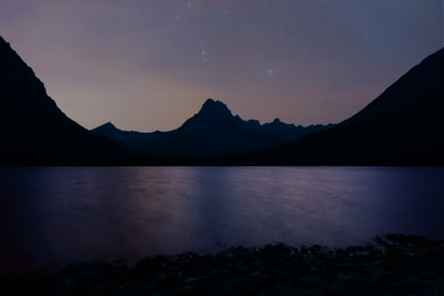 body of water near mountain glacier national park teams background